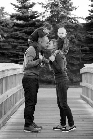 Cute couple kissing while their children look on in Brewster Gardens in Plymouth MA captured by Heidi Harting Photograph