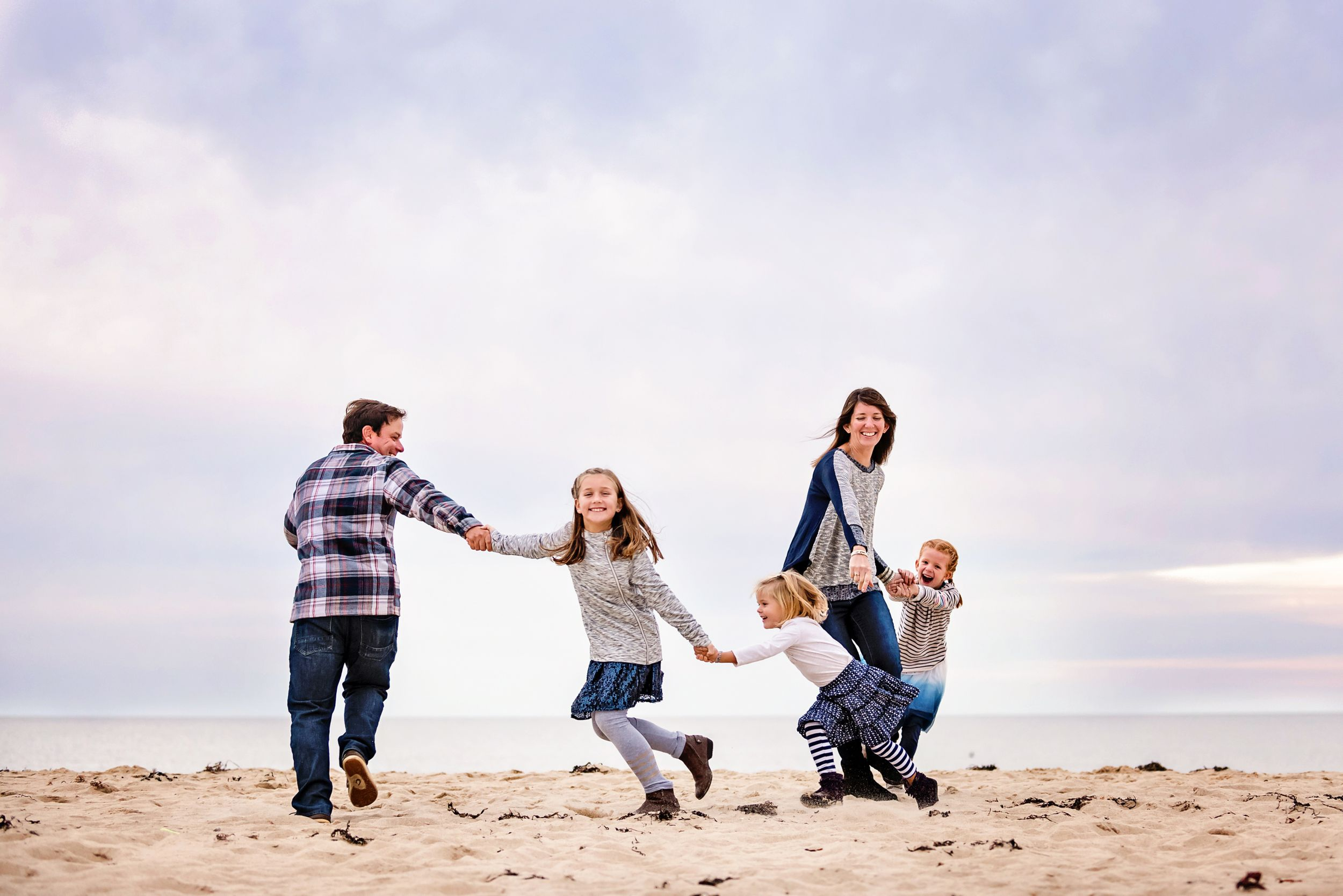 Family playing and laughing on the beach captured by plymouth, ma photographer heidi harting
