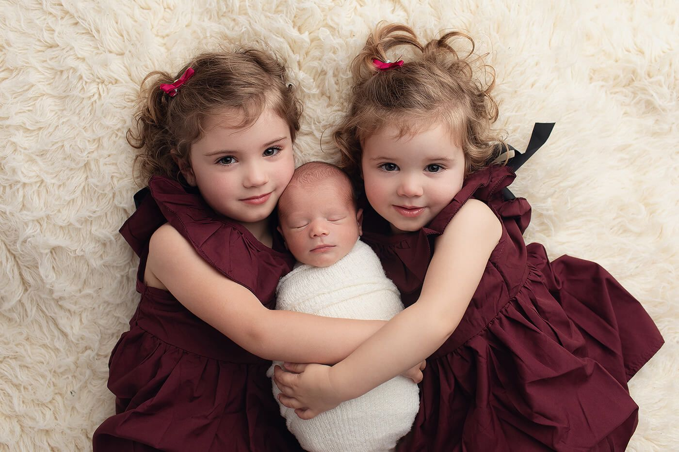 A newborn baby boy is wrapped up and lying with his two sisters having photos taken at a newborn photo studio in Perth