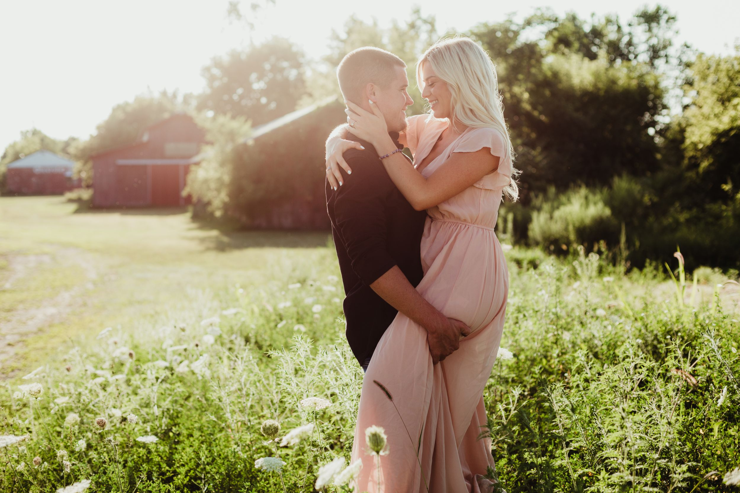 A man holding his fiance. She is wearing a long light pink dress. They are smiling at each other.