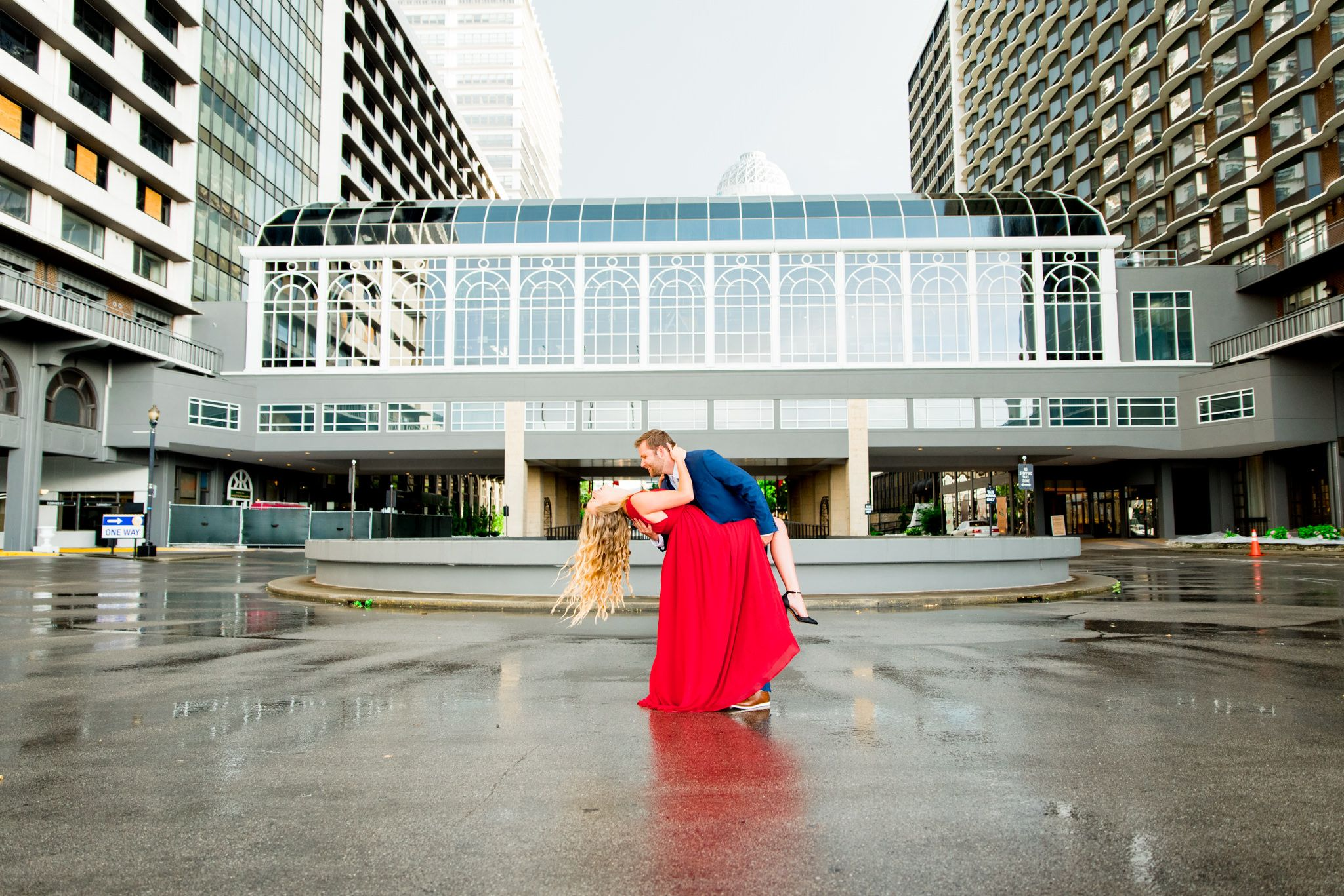 man in navy suit dipping woman in red dress with blonde hair and she laughs
