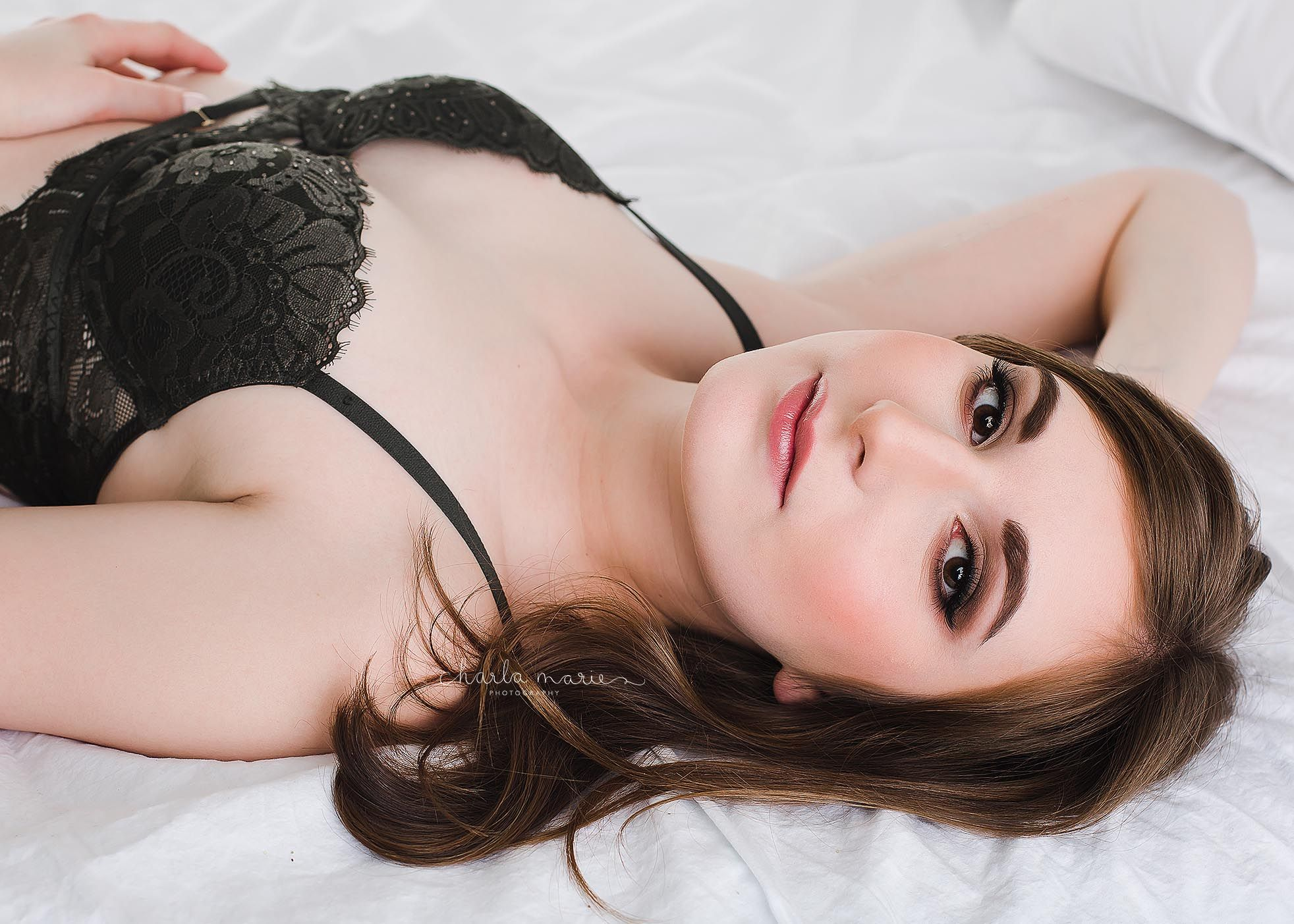 Lady laying on bed posing for boudoir session in Penticton and Kelowna B.C.