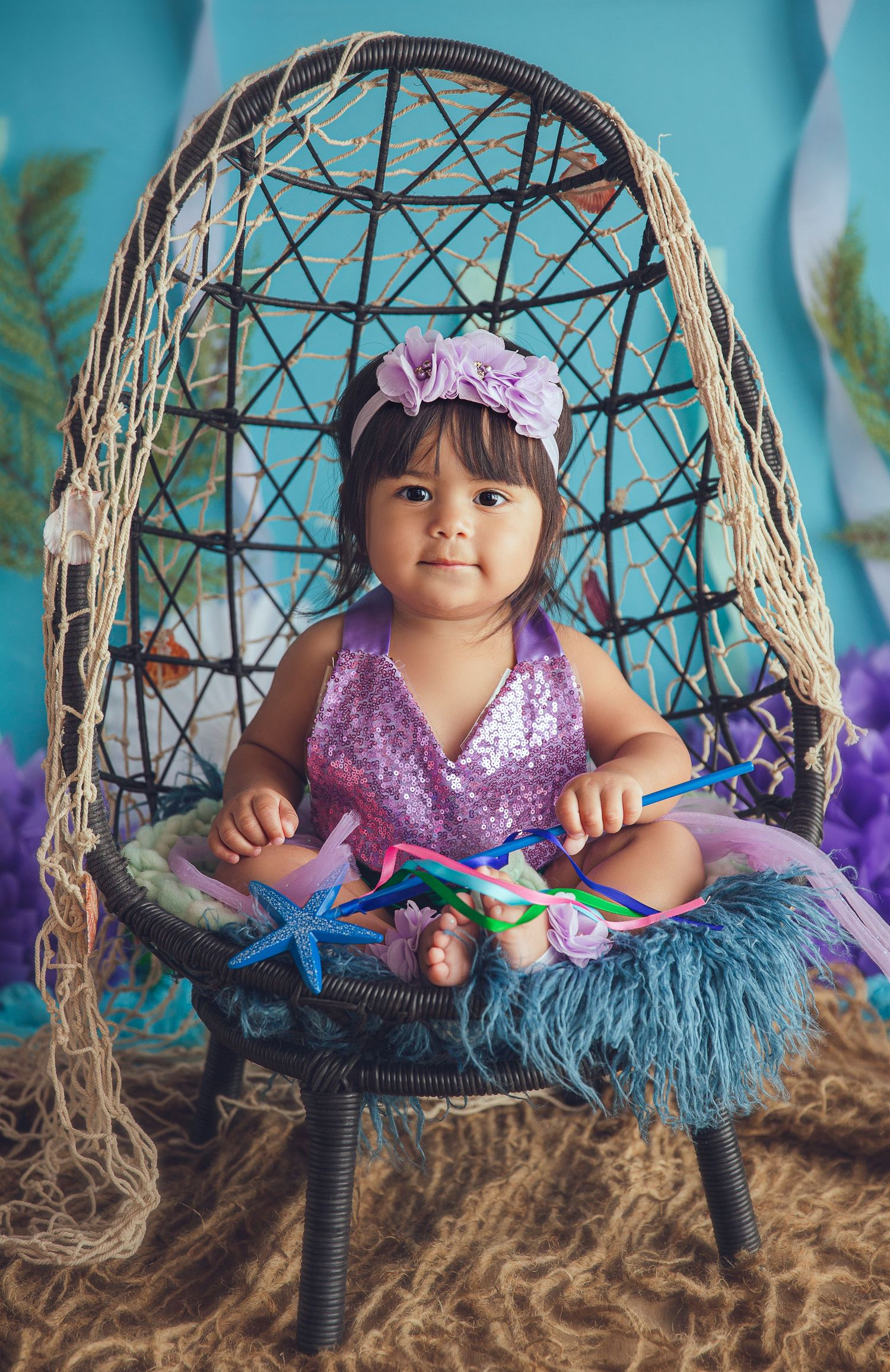 baby girl in mermaid clothing holding wand