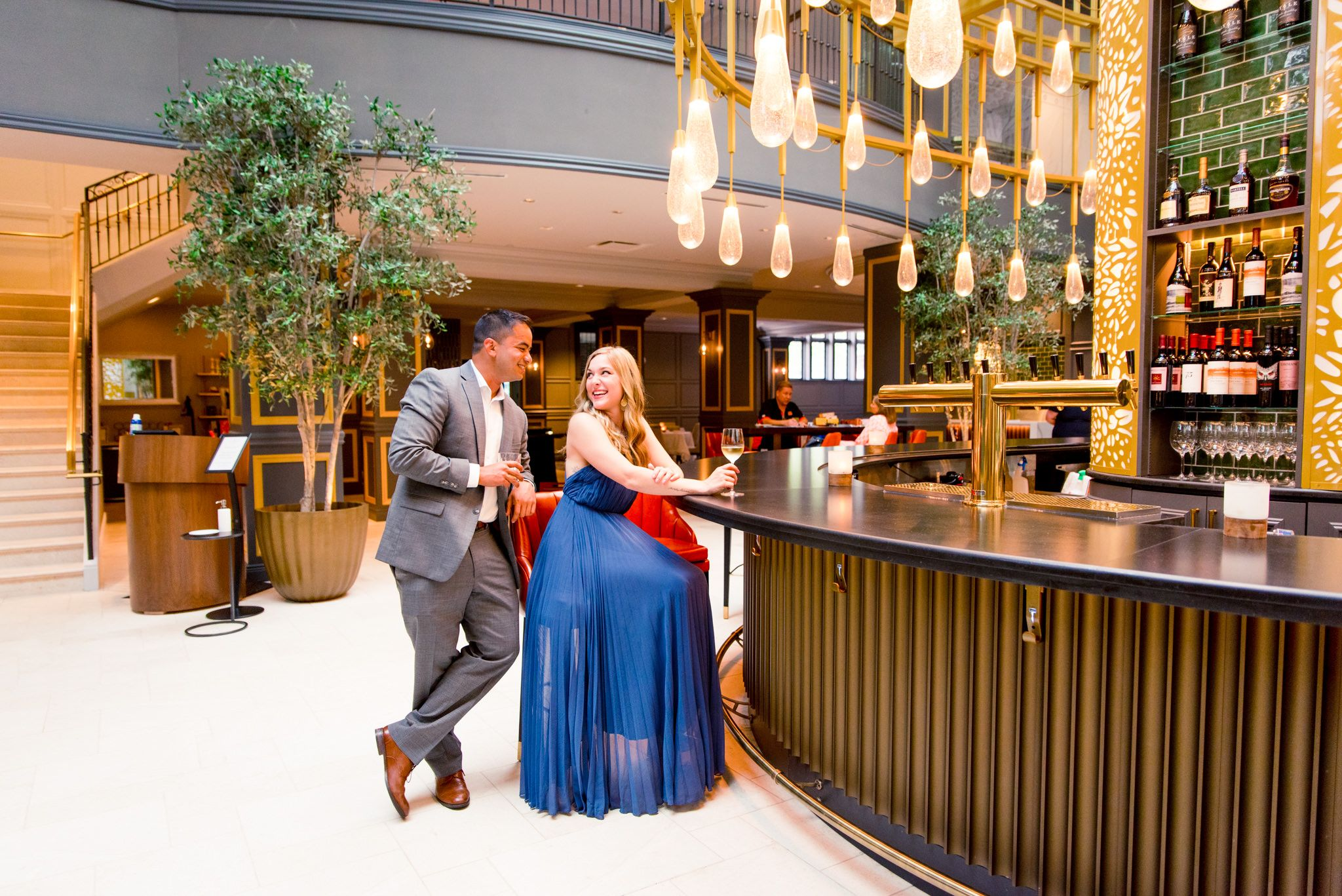blonde woman in blue dress sits at the bar at the Lytle Park Hotel, laughing with fiance in grey suit standing behind