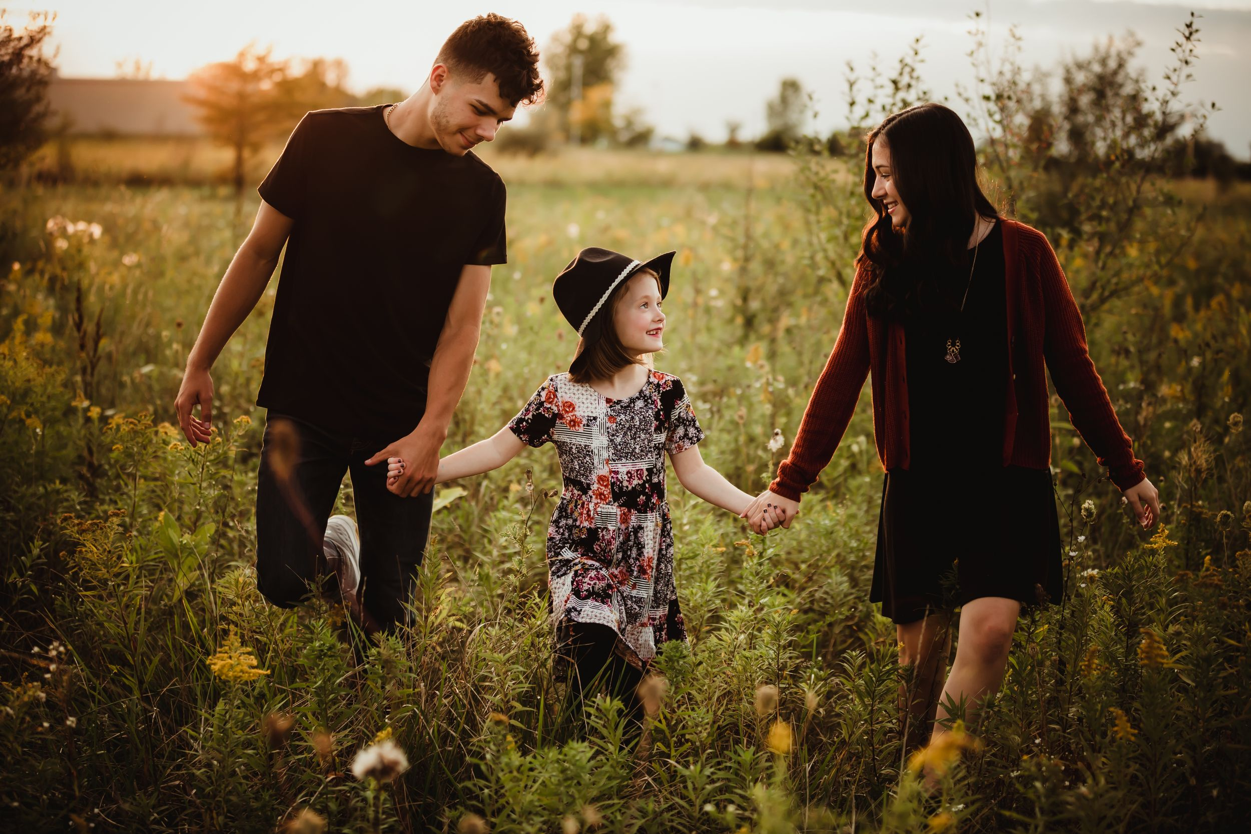 Older son and daughter holding younger daughter's hand and walking though a field at sunset.