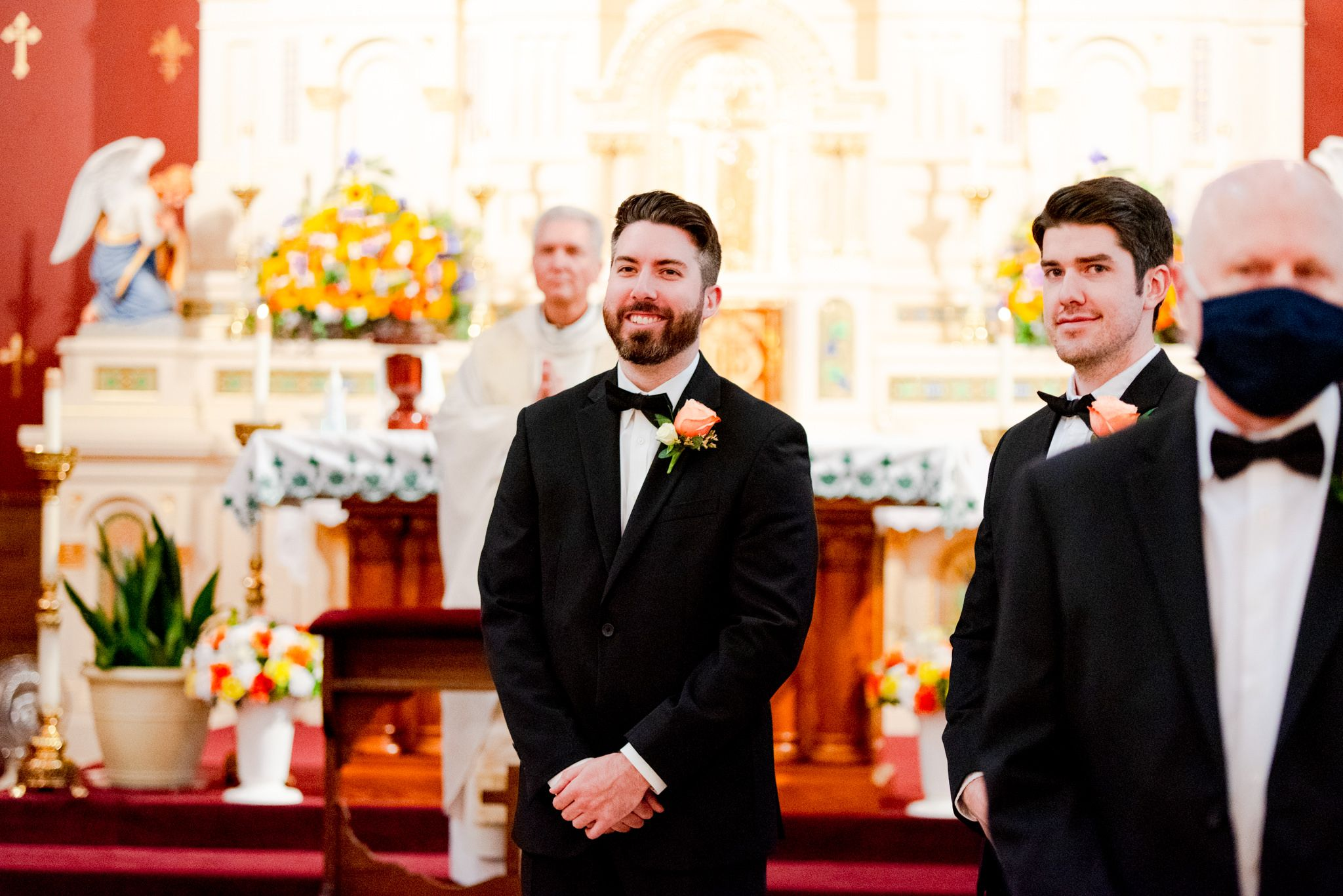 brunette groom and his brother watching the bride walk down the aisle of the church, both smiling at her