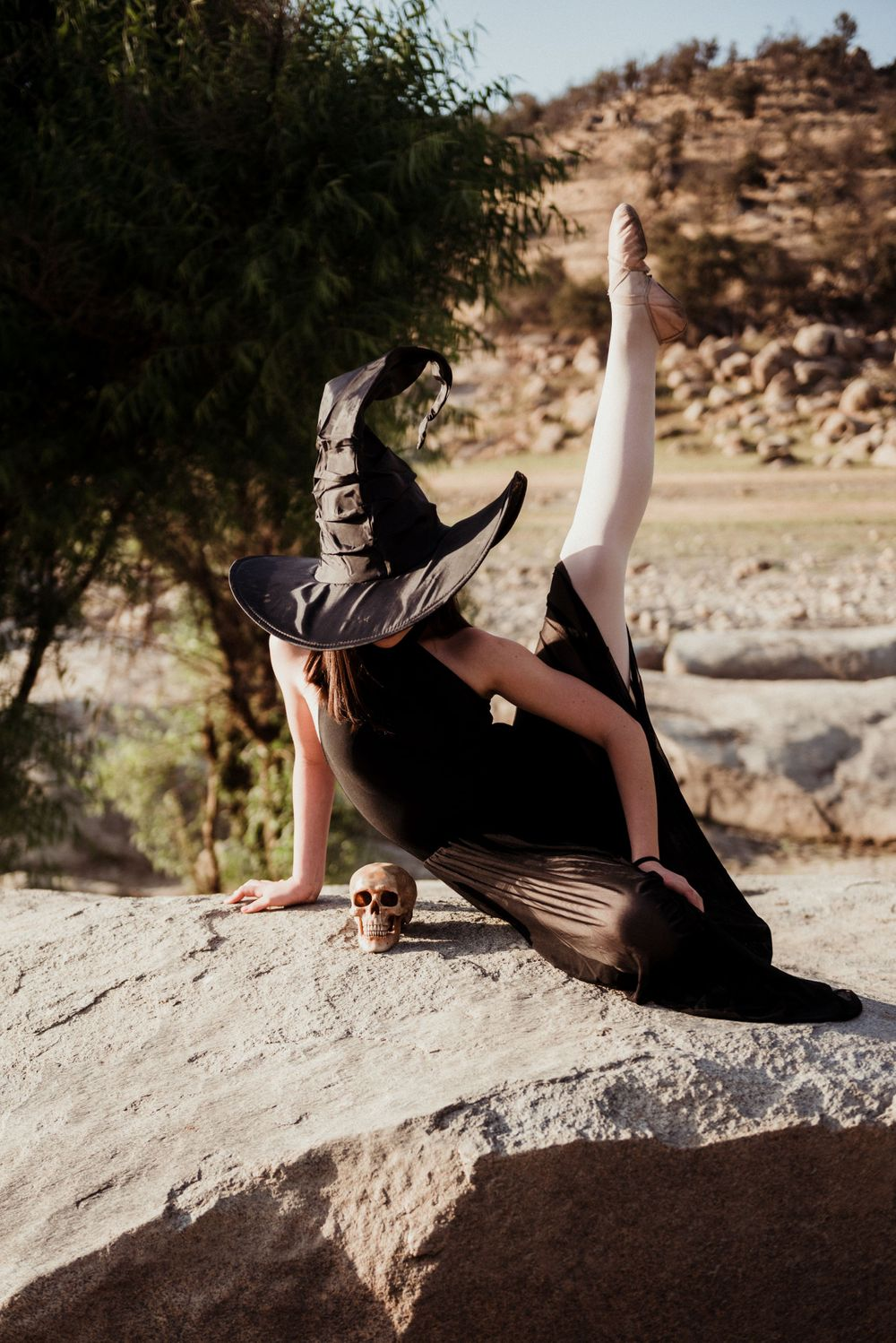 Girl dressed like a witch and posing on a boulder next to a skull for a Halloween photoshoot in Three Rivers California