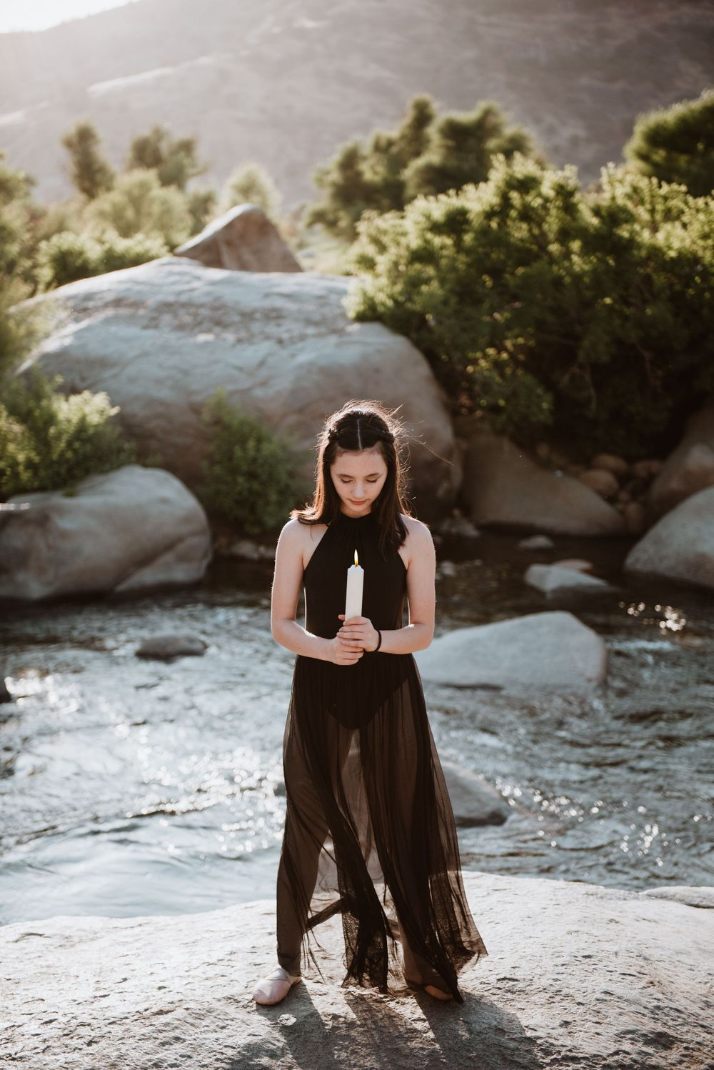 Girl posing with a lit candle during a river photography session for Halloween; Three Rivers, California
