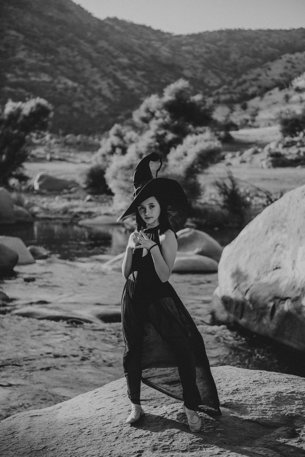 Girl posing in a witch's hat in front of the river; Halloween photoshoot in Three Rivers, California