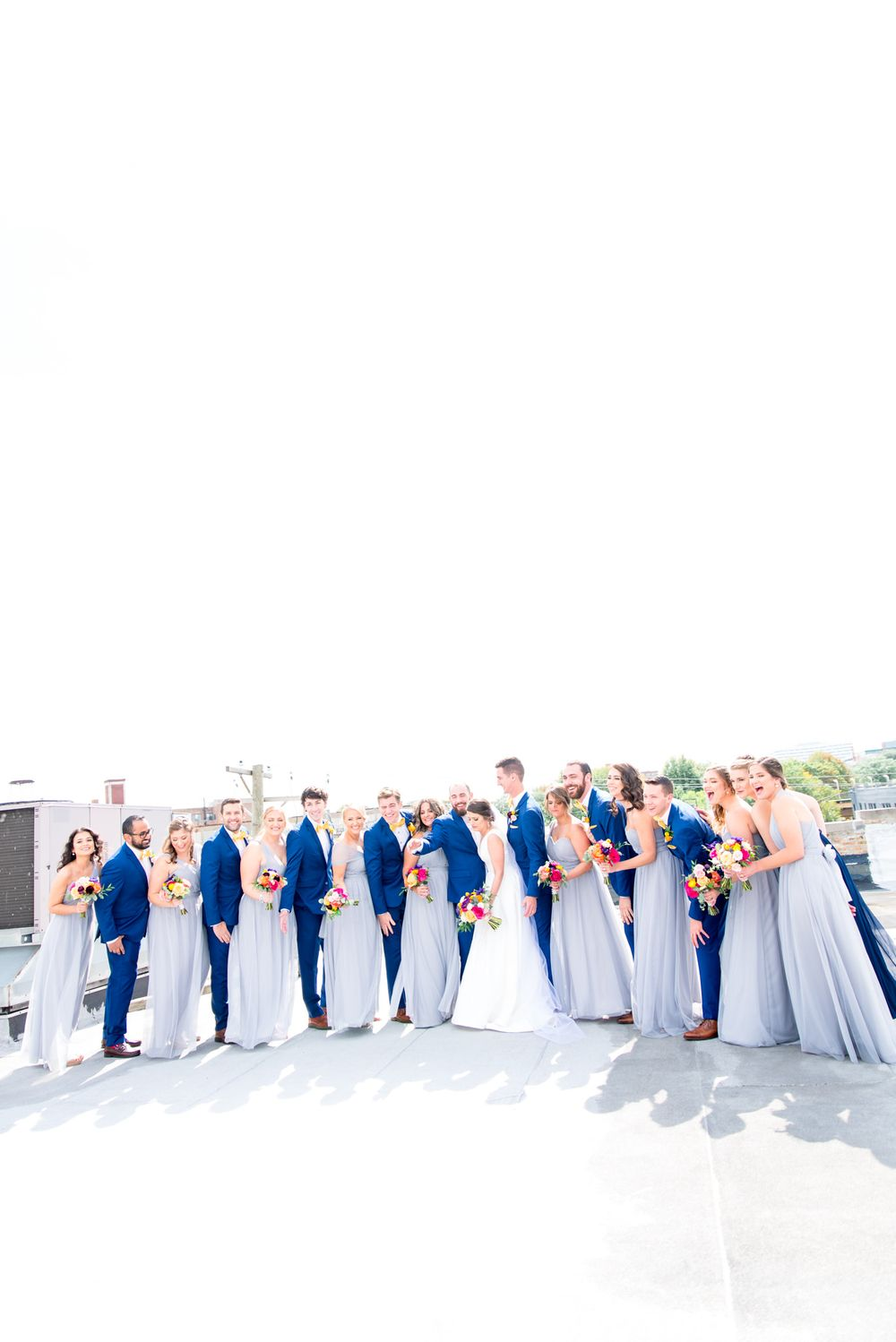 wedding party in light blue and navy blue on the rooftop of Room 1520 for a fall wedding