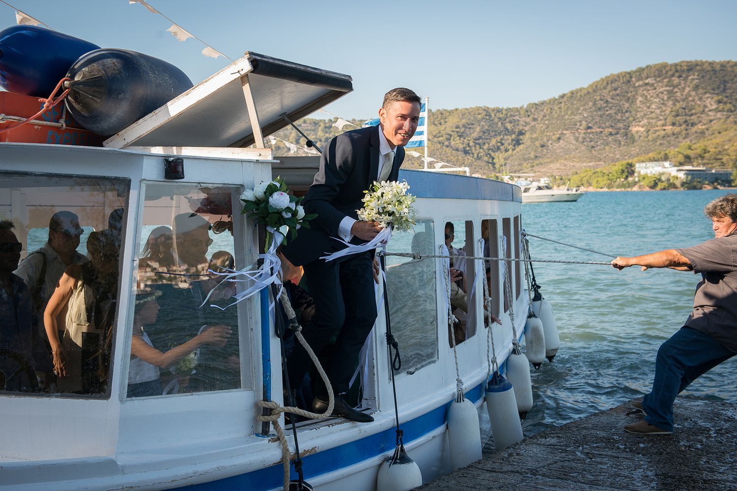 smiling groom gets out of the boat which brought him to the wedding ceremony place