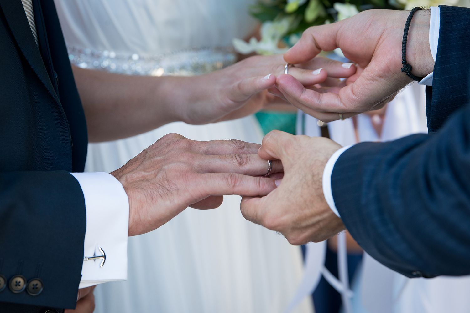 couple's and bestman's hands during the rings exchange