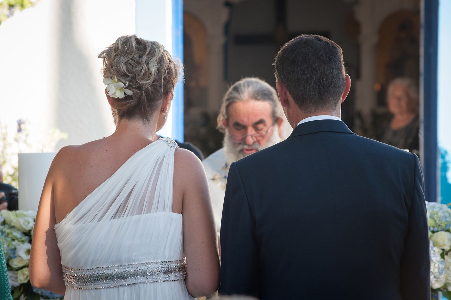 priest among couples shoulders during wedding ceremony
