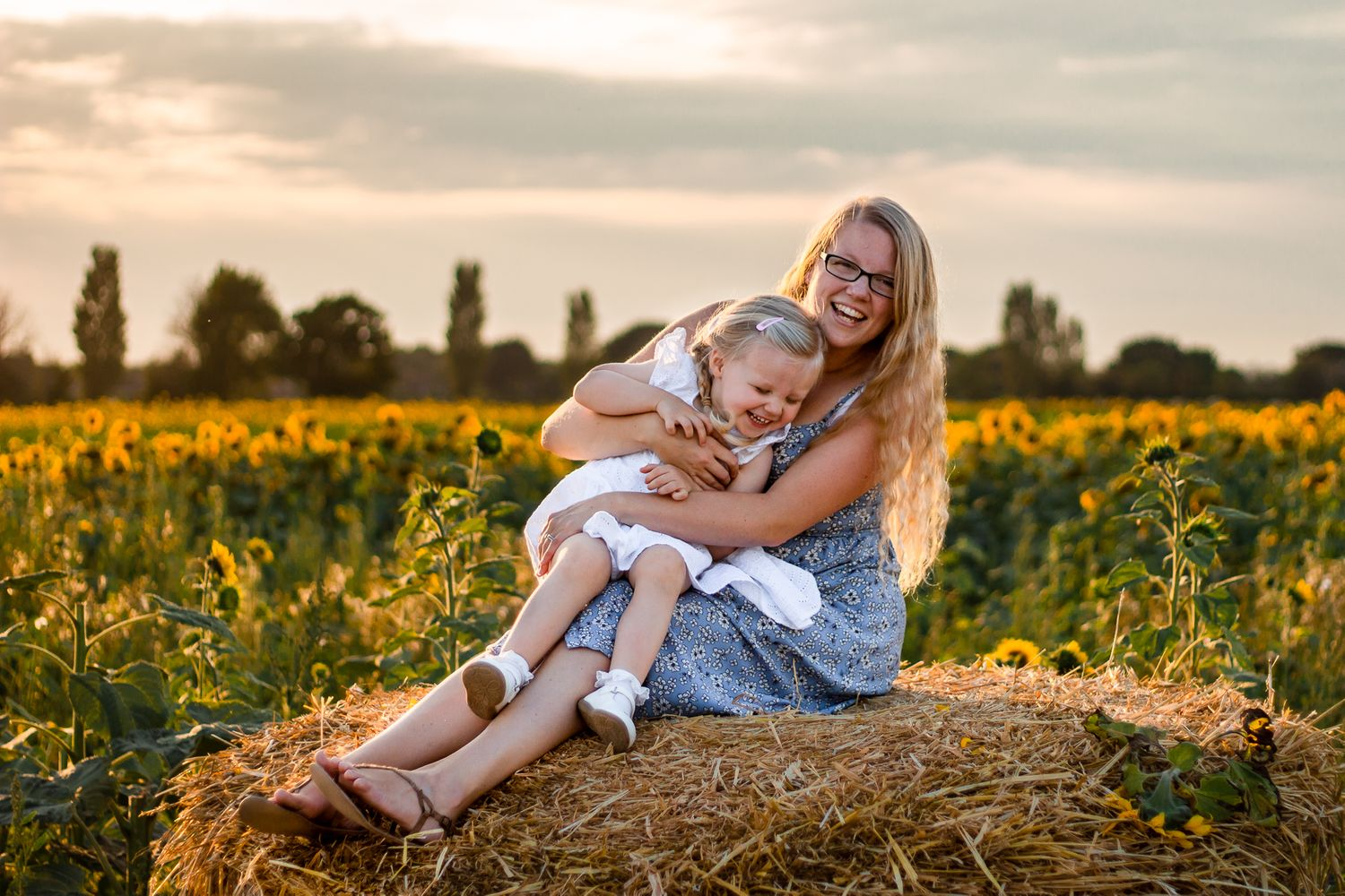 In a sunflower field on Hayling Island at sunset a Mum and her 2 year old daughter sit on a haybale laughing.