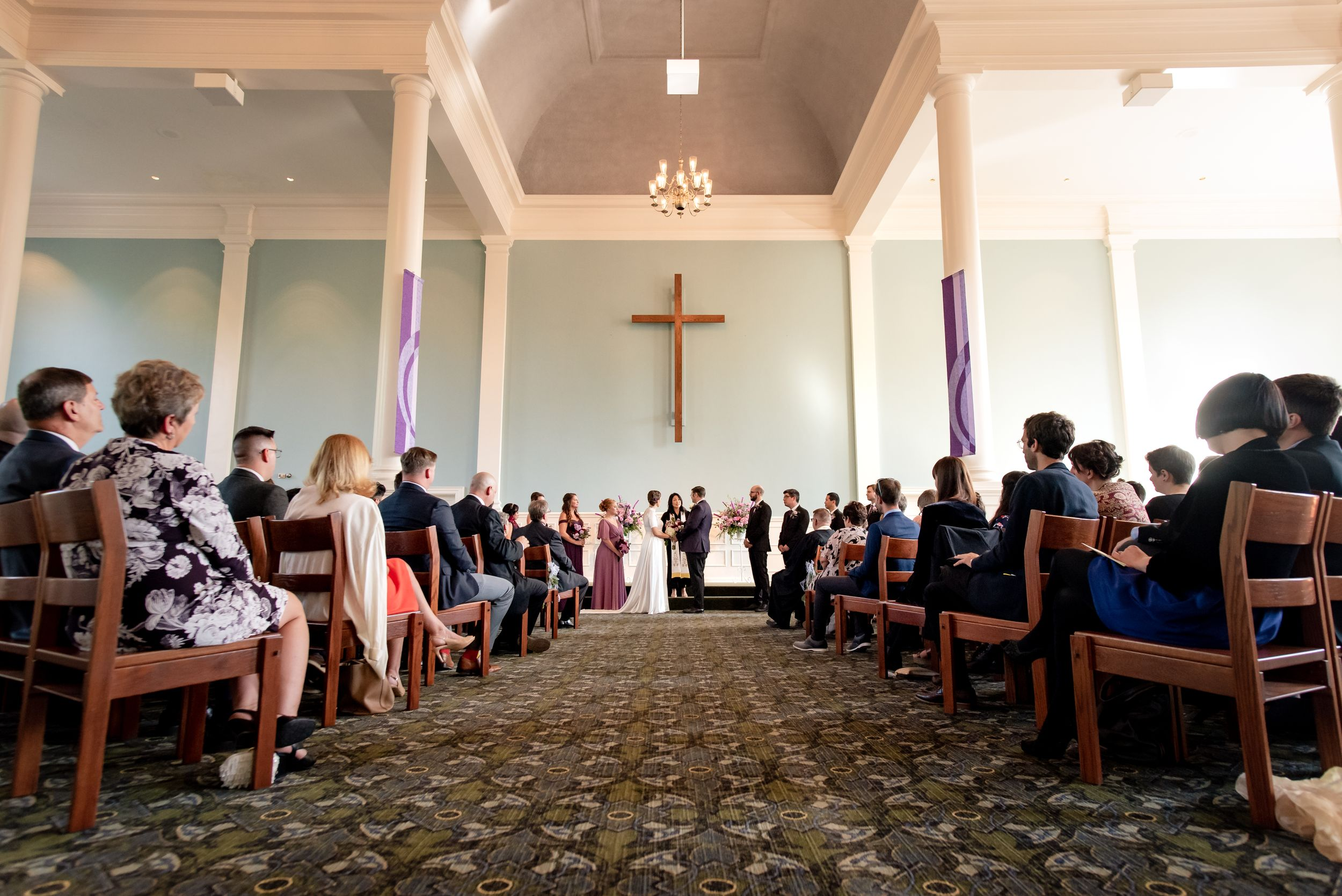 wedding ceremony in church with couple standing with officient under large cross shot in wide angle to see guests