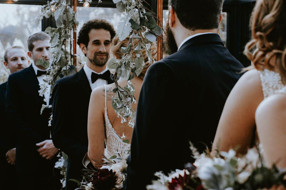 Groom looking at bride with bridal party surrounding them during Jewish wedding ceremony