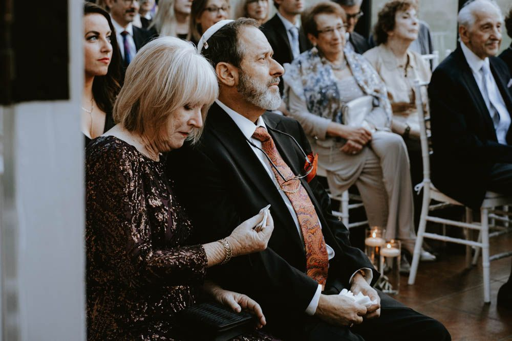 mother of the bride wiping tears away during Jewish wedding ceremony