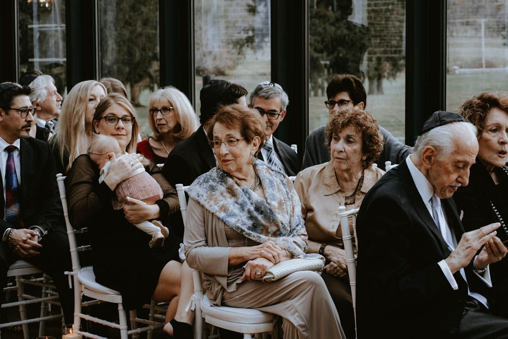 grandmother and family watching as bride walks down aisle in green house ceremony at The Highlands in New York