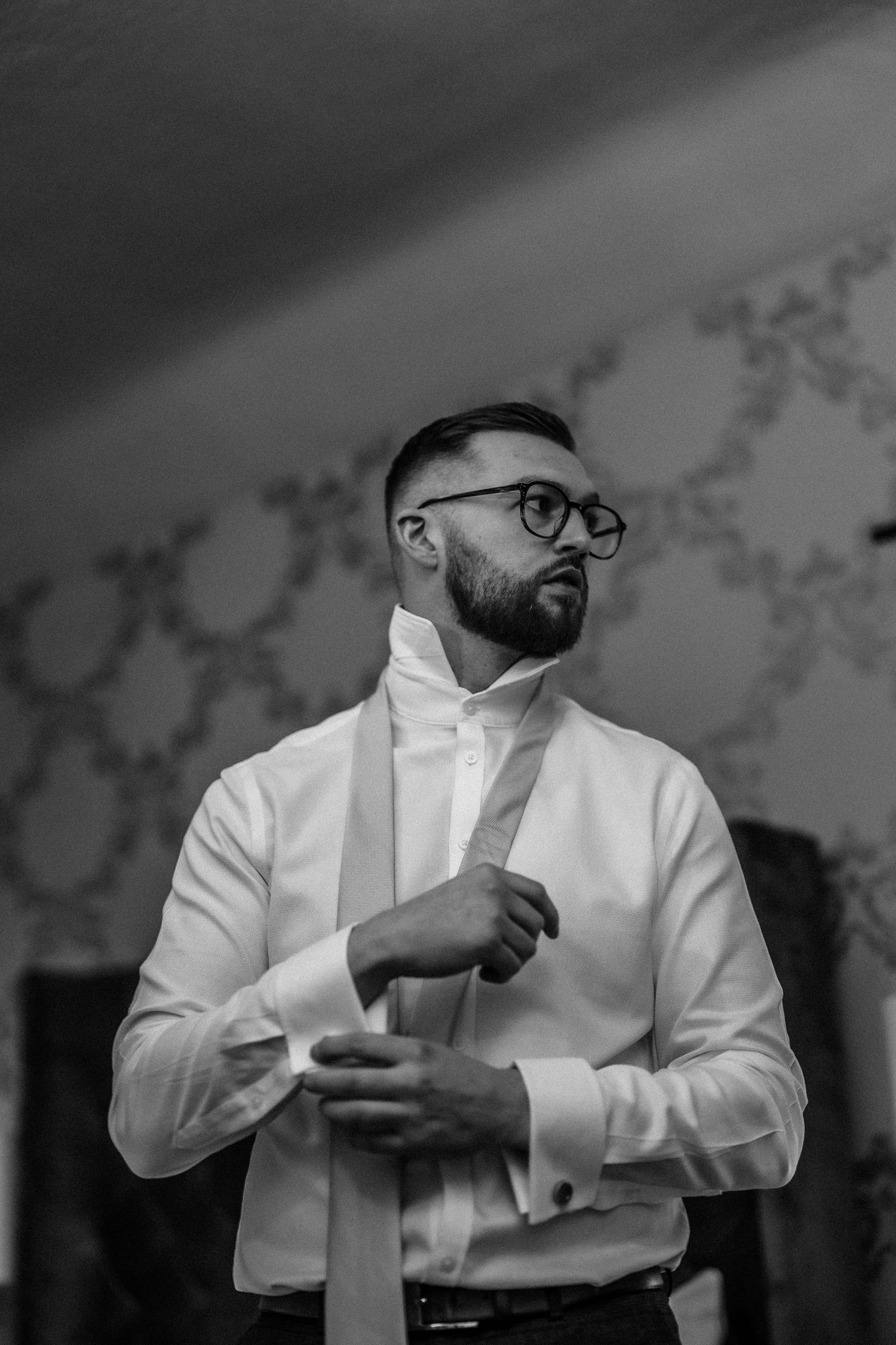 Black and white photo of groom getting ready at wedding in Wales