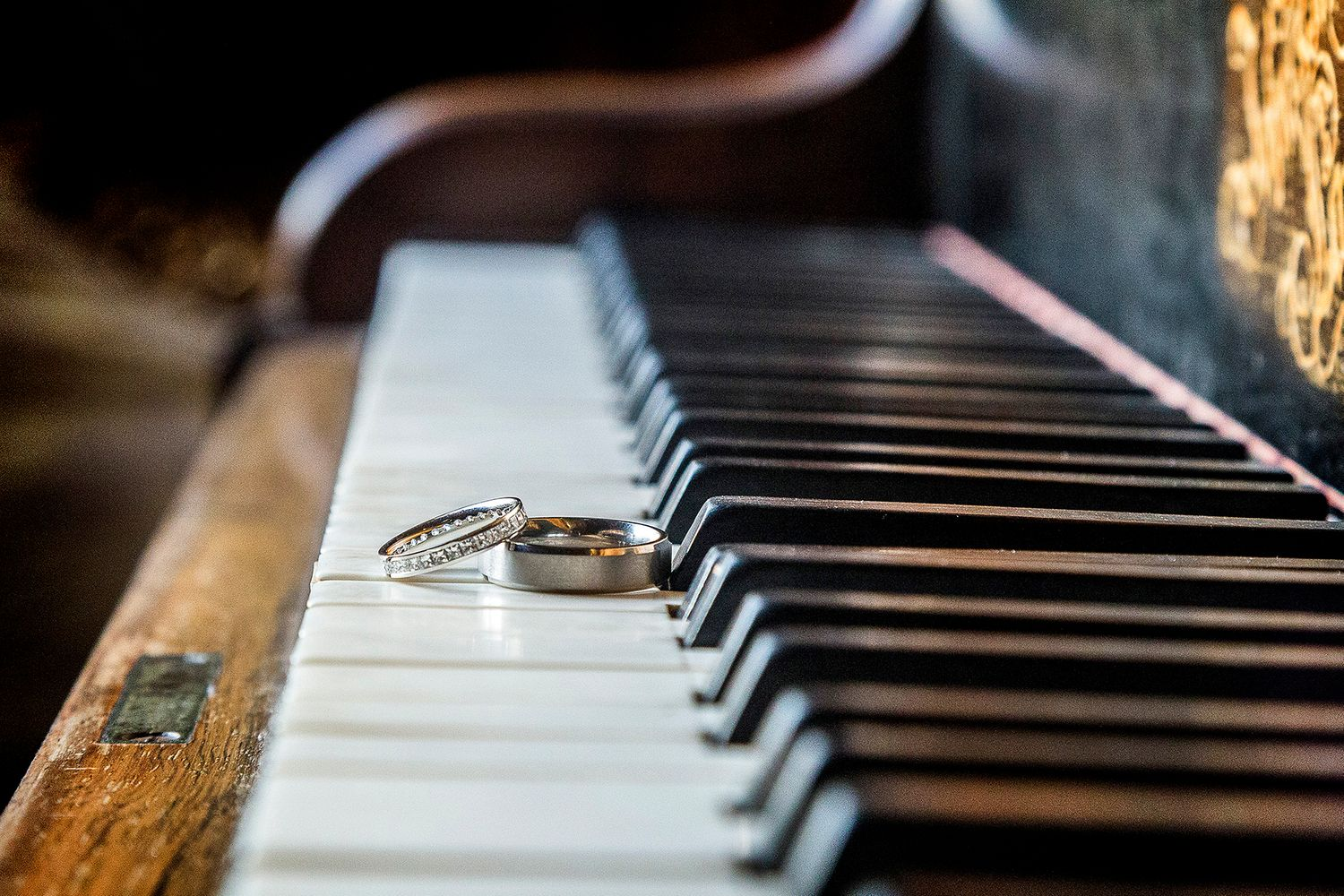 wedding rings positioned on piano keys