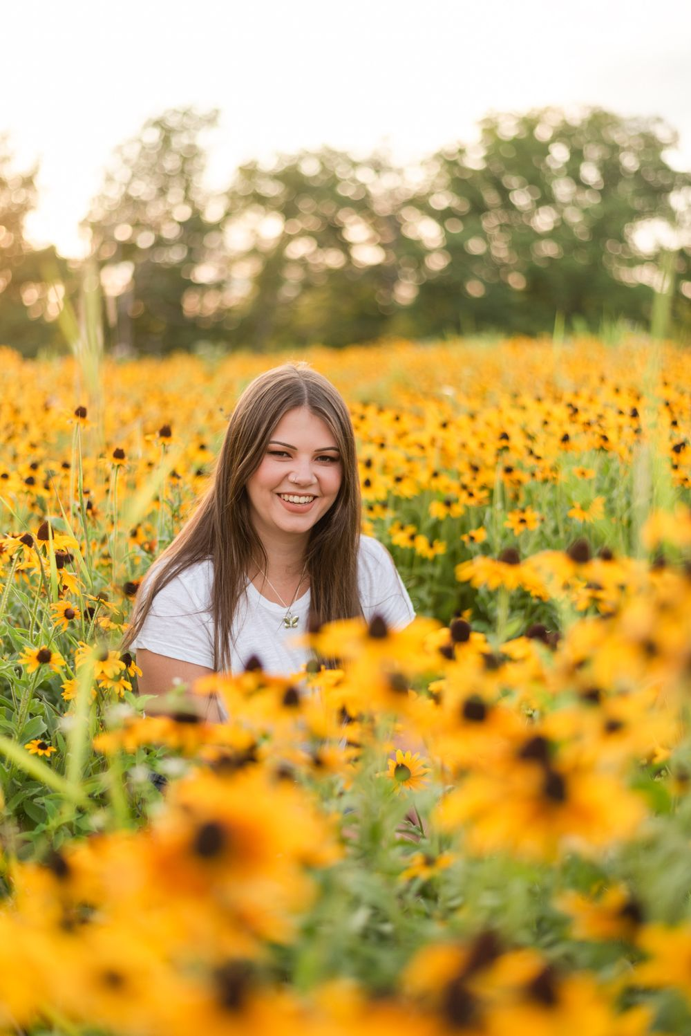 Senior sitting in flower patch in golden sunlight at Hartwood Acres in Pittsburgh Pennsylvania
