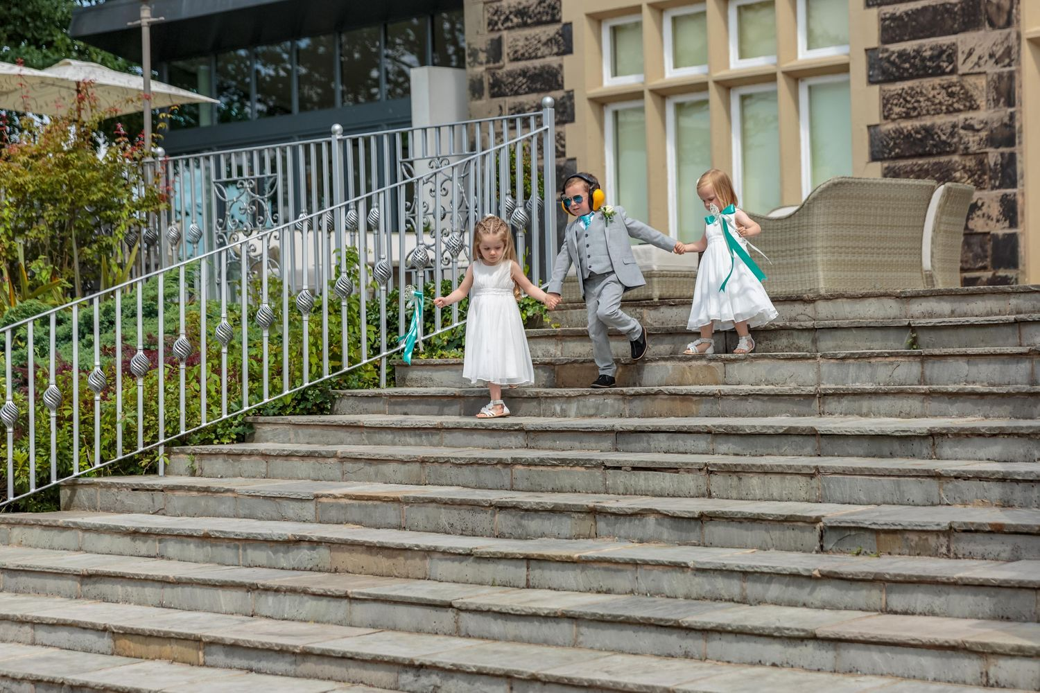 young page boy wearing ear defenders walking down the steps outside west tower holding hands with the flower girls