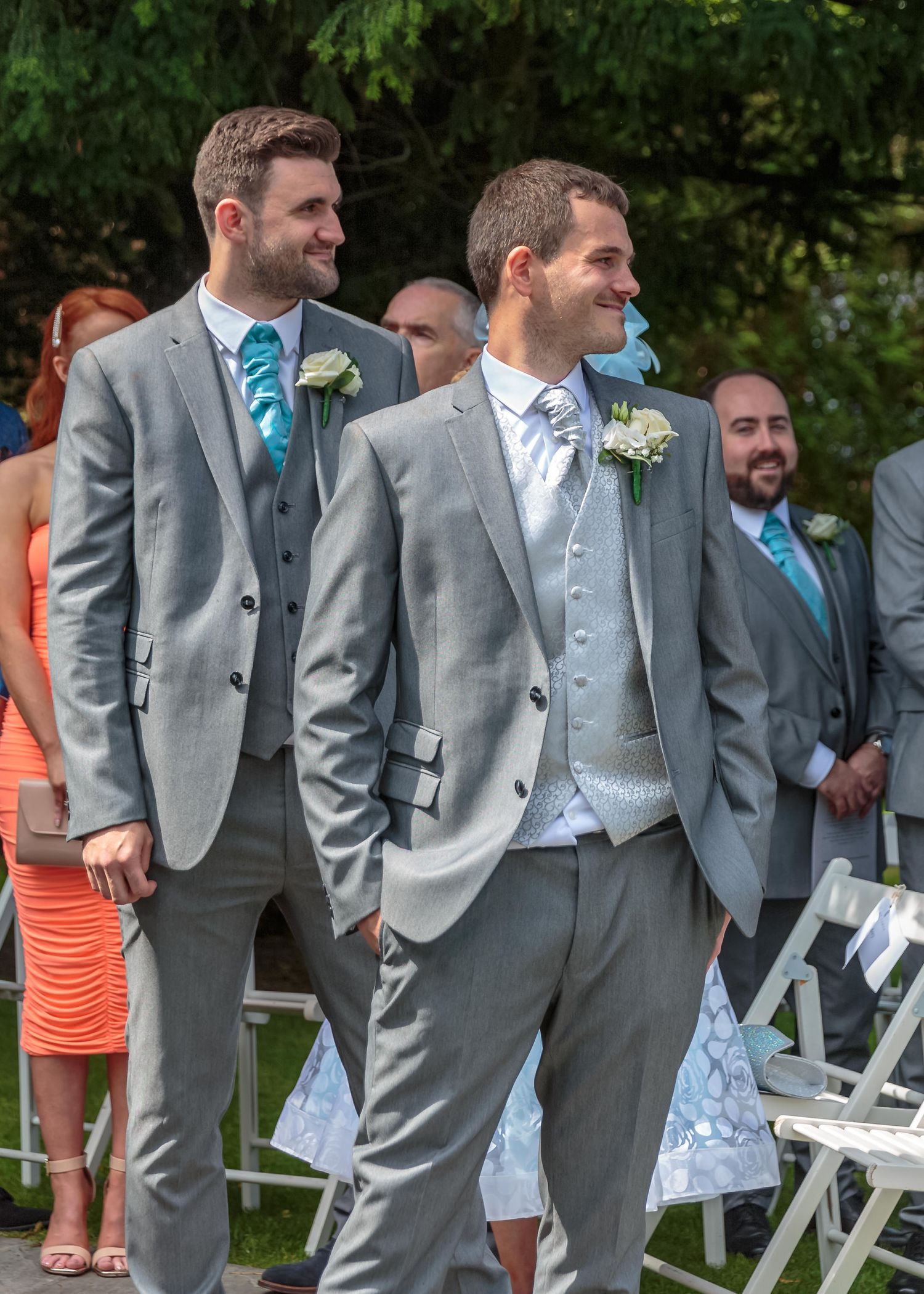 groom stood with his best man smiling as he looks back up the aisle at his bride
