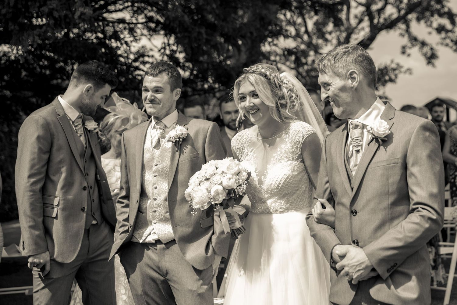 bride smiling as she arrives at the top of the aisle arm in with her father in the garden at west tower aughton