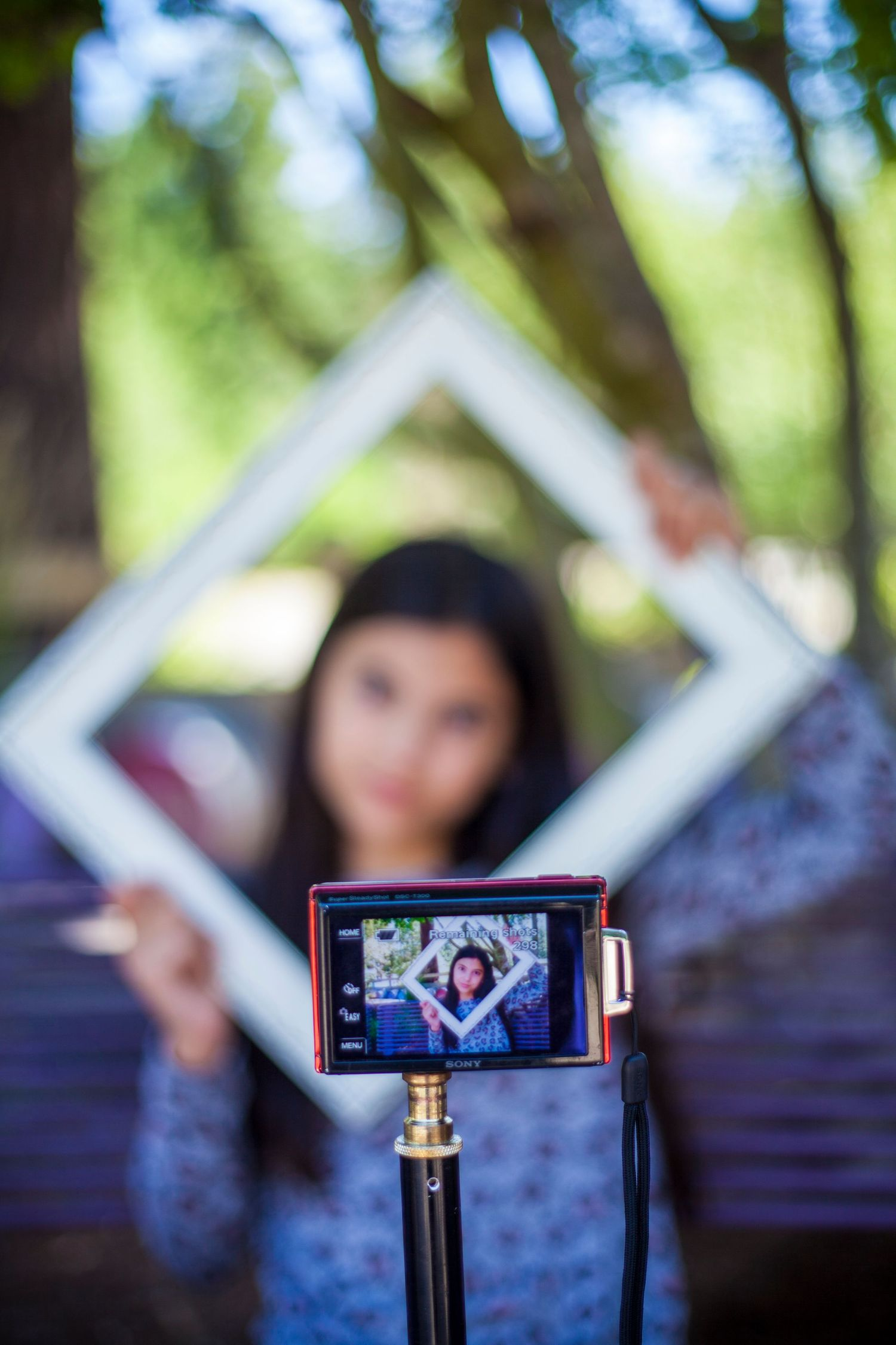 girl holding a picture frame taking a selfie with a camera on a tripod.