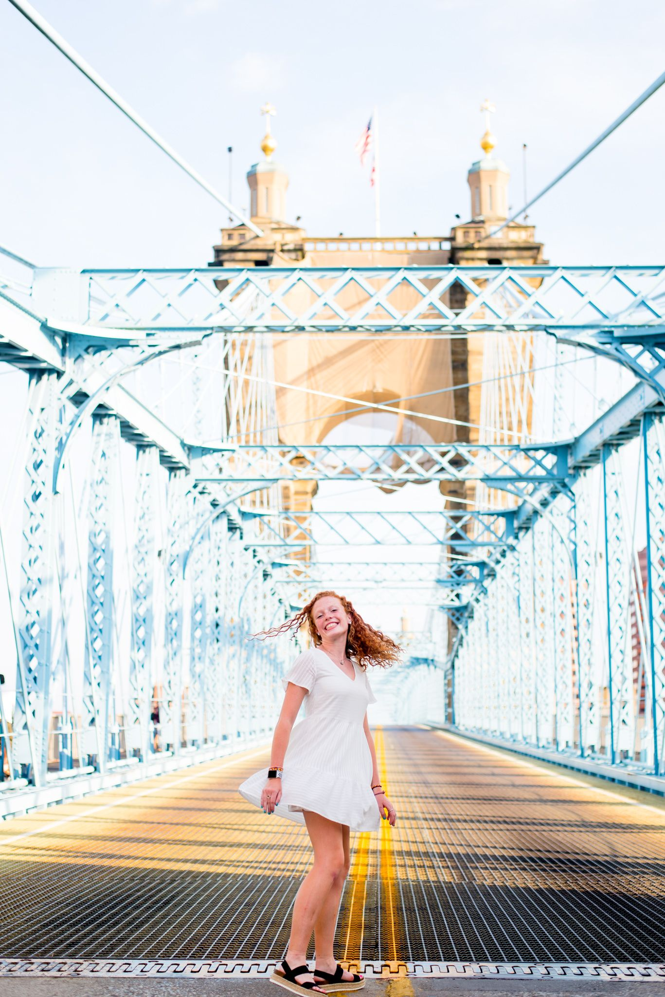 young woman with red curly hair in a white dress spinning around in the middle of Roebling Bridge for senior pictures