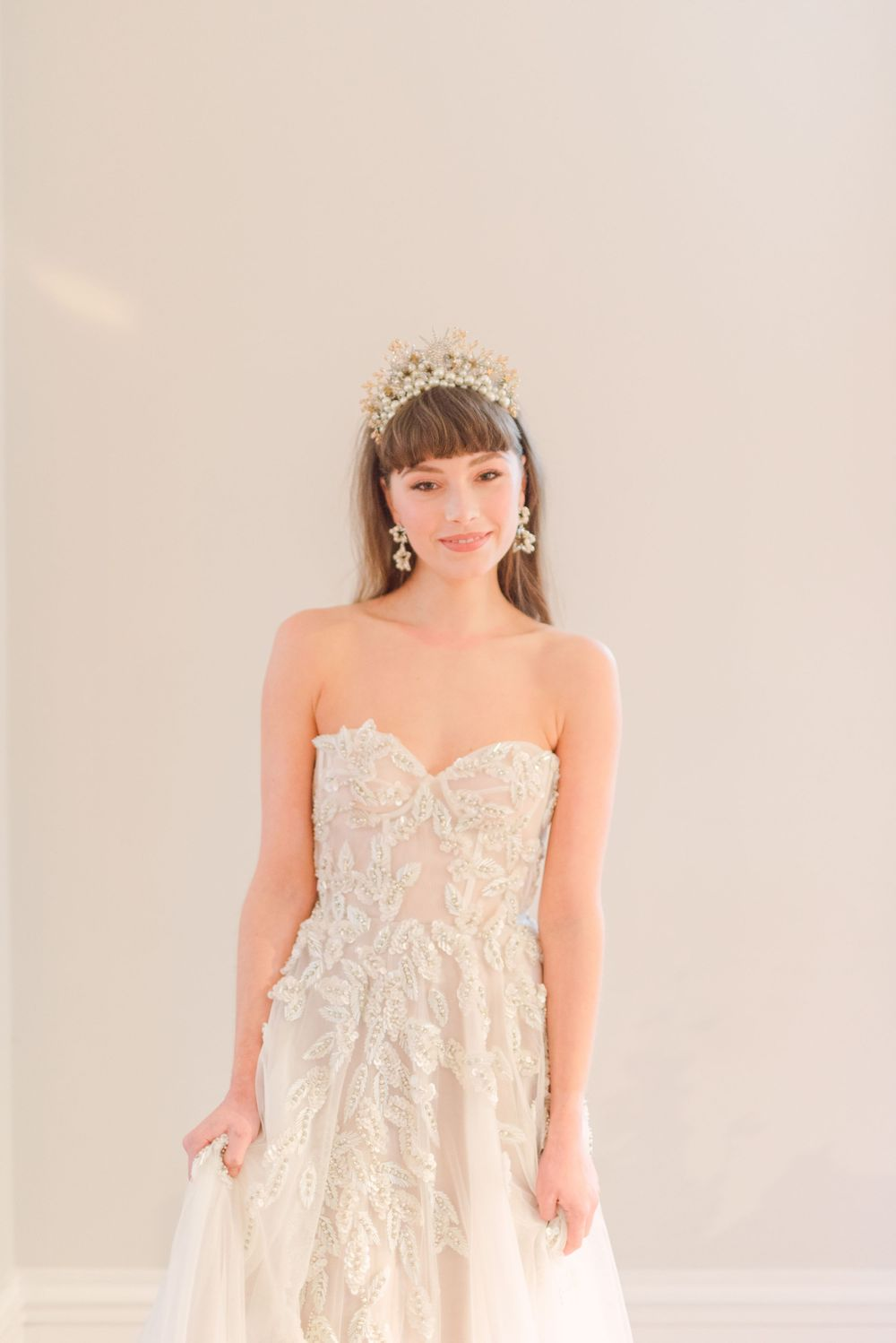 modern bride wearing embellished beaded Emma Beamont wedding dress with statement celestial star crown