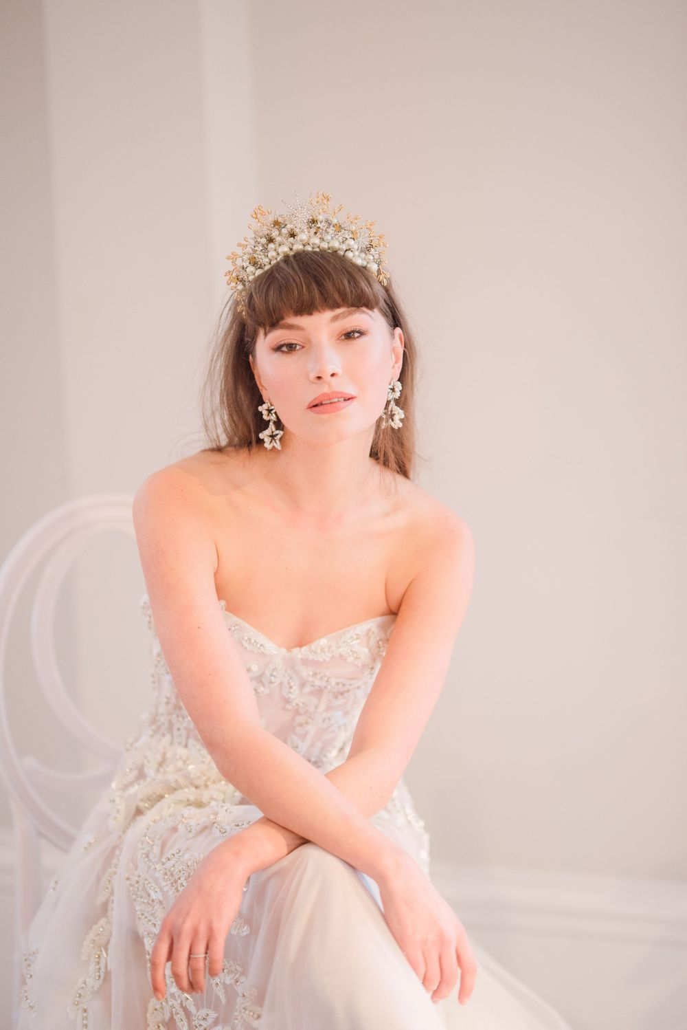 modern bride wearing beaded Emma Beamont wedding dress with statement celestial star crown and star earrings