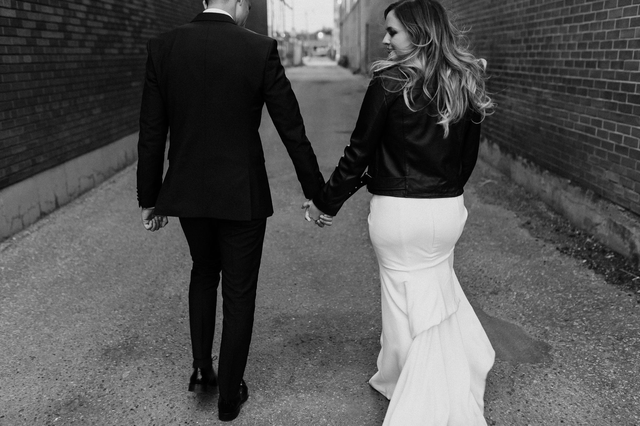 Black & white photo of bride and groom walking in Toronto alley holding hands with wind in the hair and wedding dress.