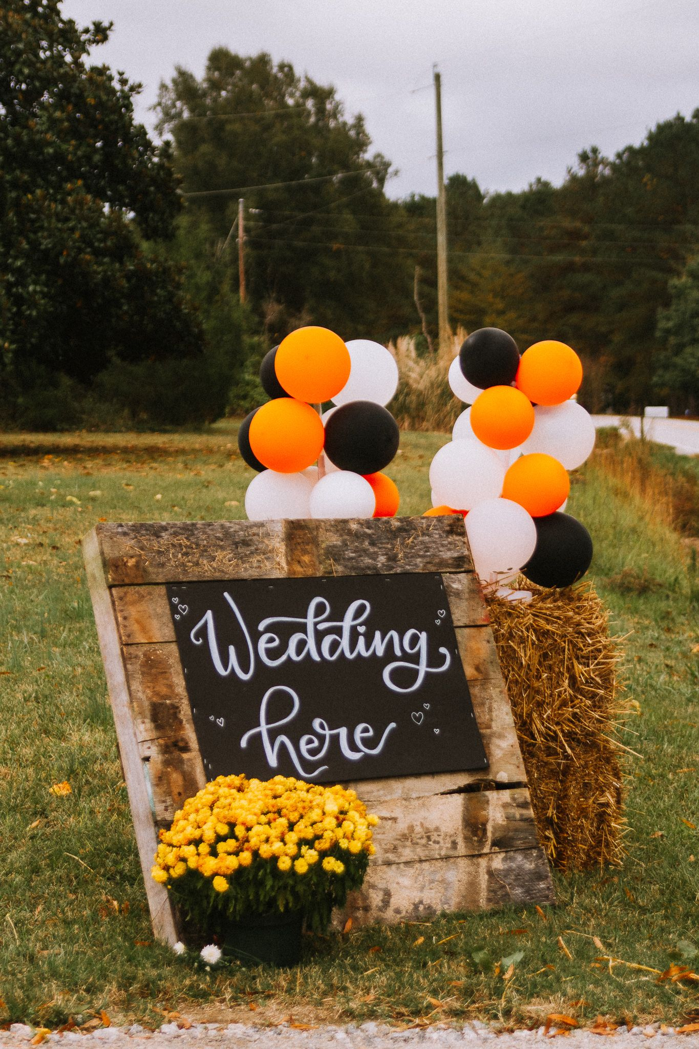 wedding sign in front of hay bales with orange black and white balloons