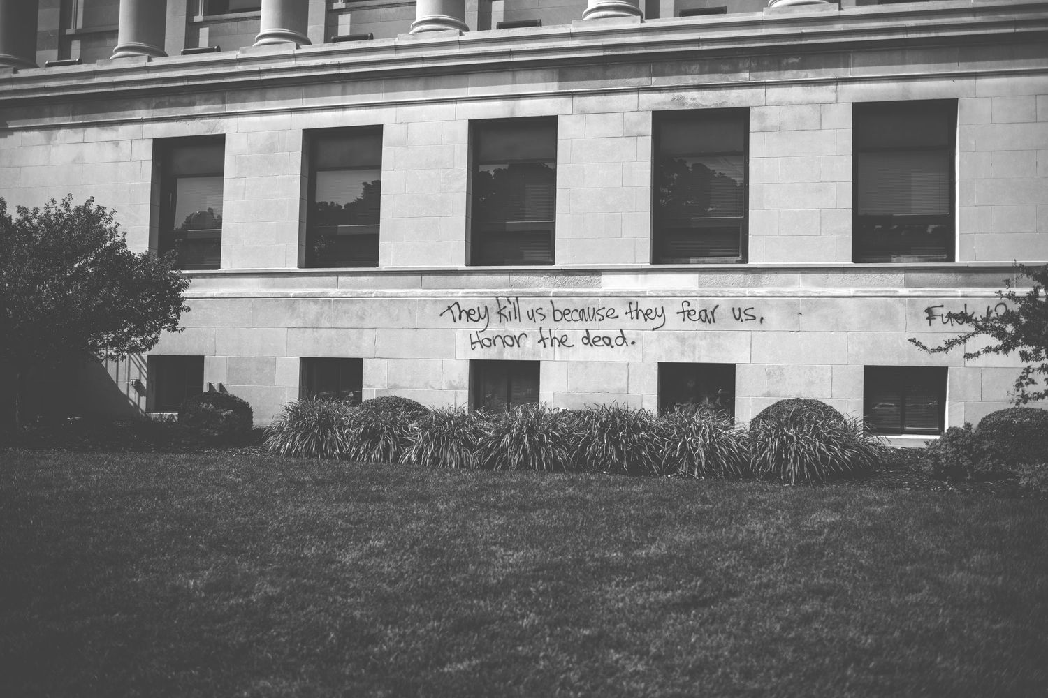 "In spray paint, ""They kill us because they fear us. Honor the dead."" is written on the Kenosha County Courthouse."