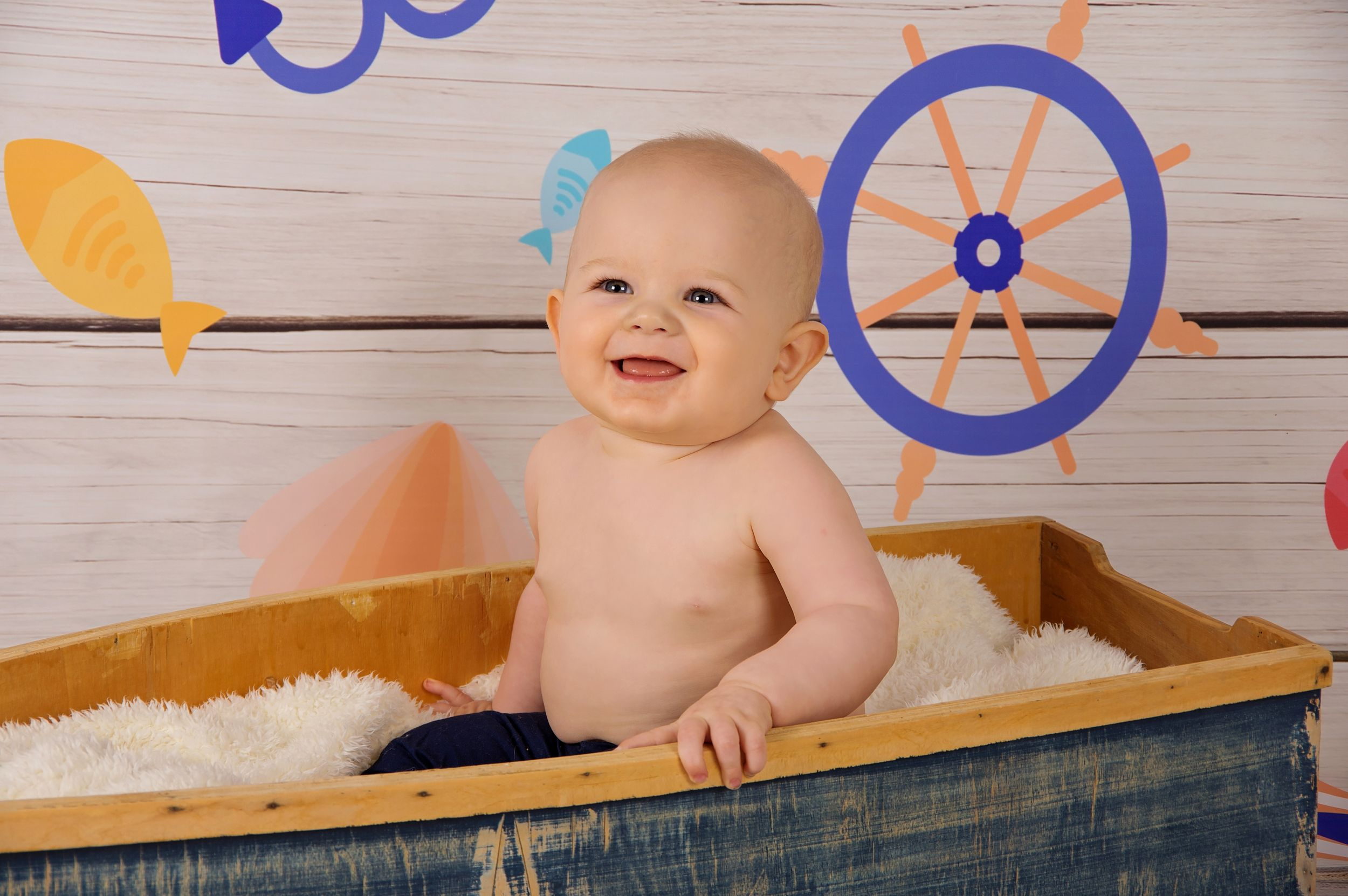 baby boy in wooden boat smiling