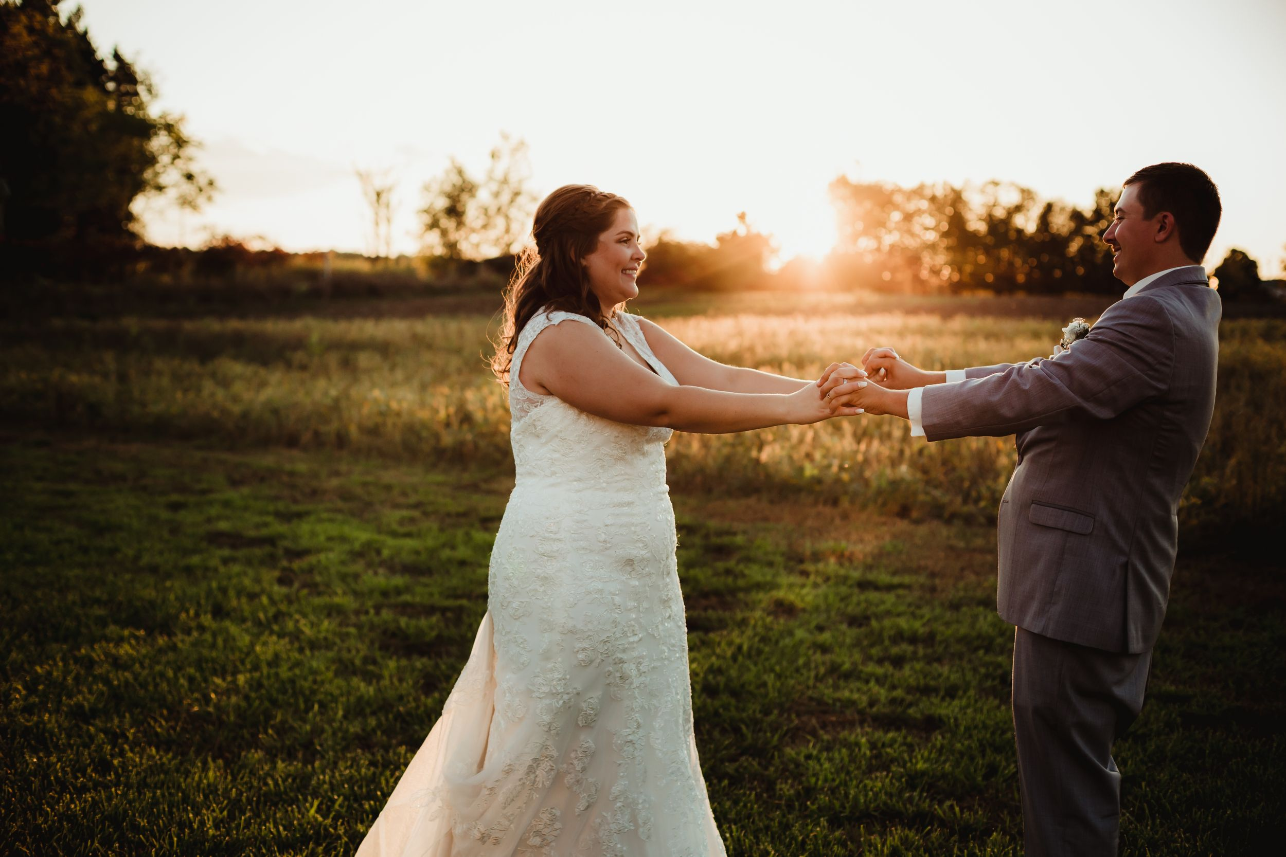 Bride and groom with hands laced together smiling at each other in front of a field at sunset.