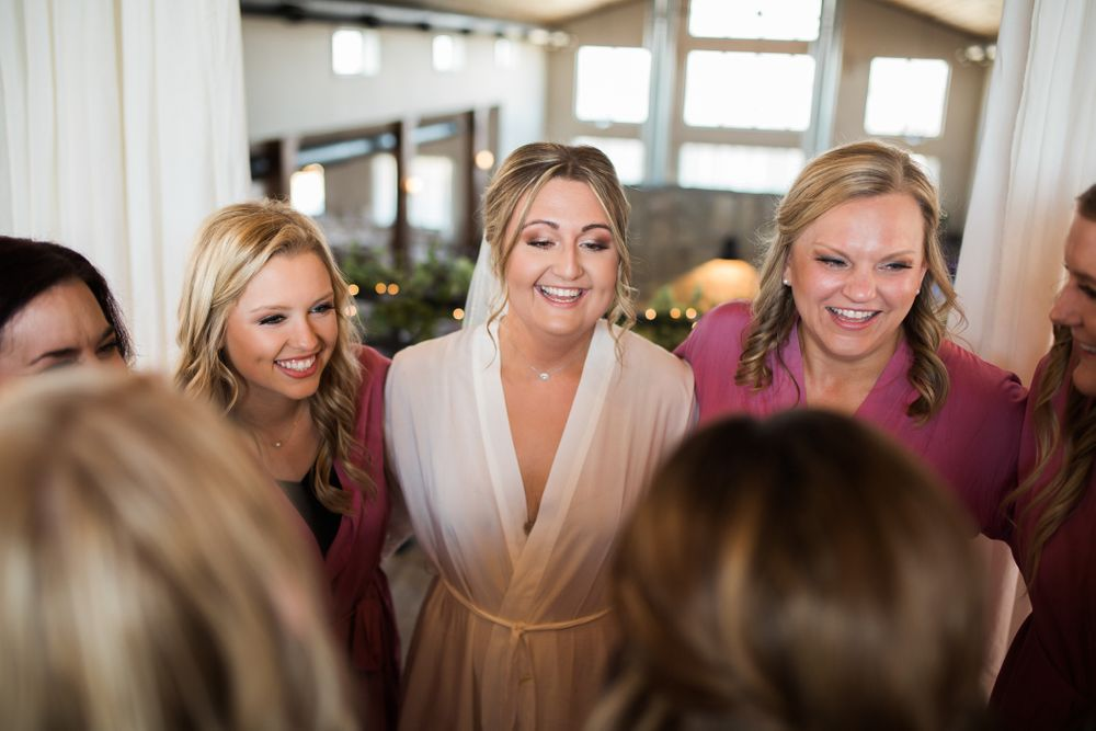 Bridesmaids giving the bride a group hug in the bridal suite at Eagle Bluff Ranch in Waverly, MO.