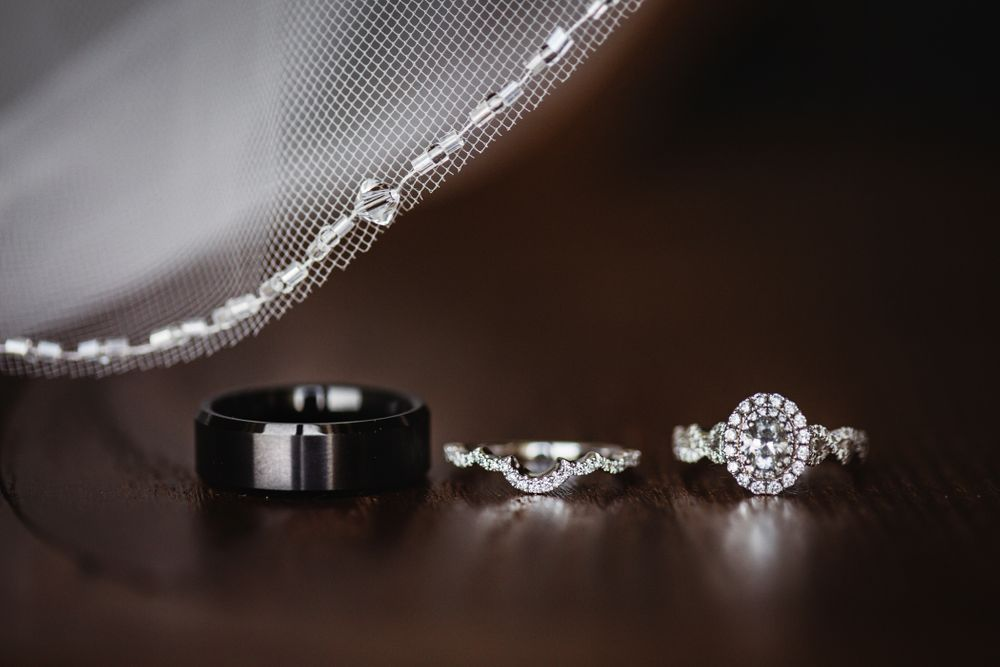 Three wedding rings.  The groom's wedding band with the bride's rings.  The veil is in the background of the ring shot.