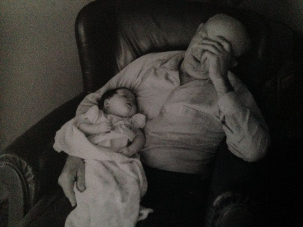 Older father holds baby daughter