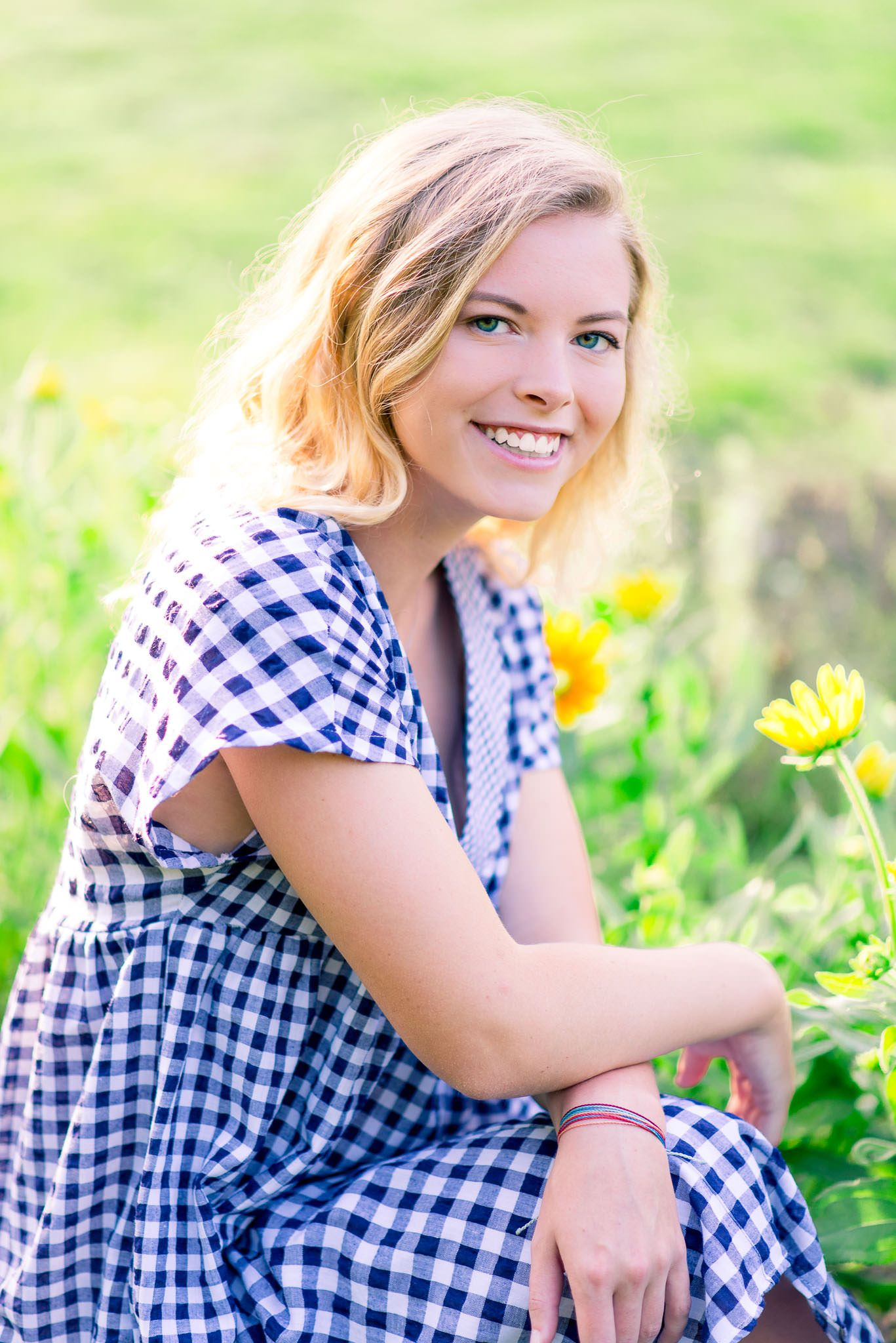 young blonde woman with blue eyes smiling and crouching in front of flowers in the summer