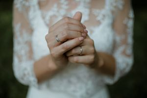 Engagement ring and lace wedding gown