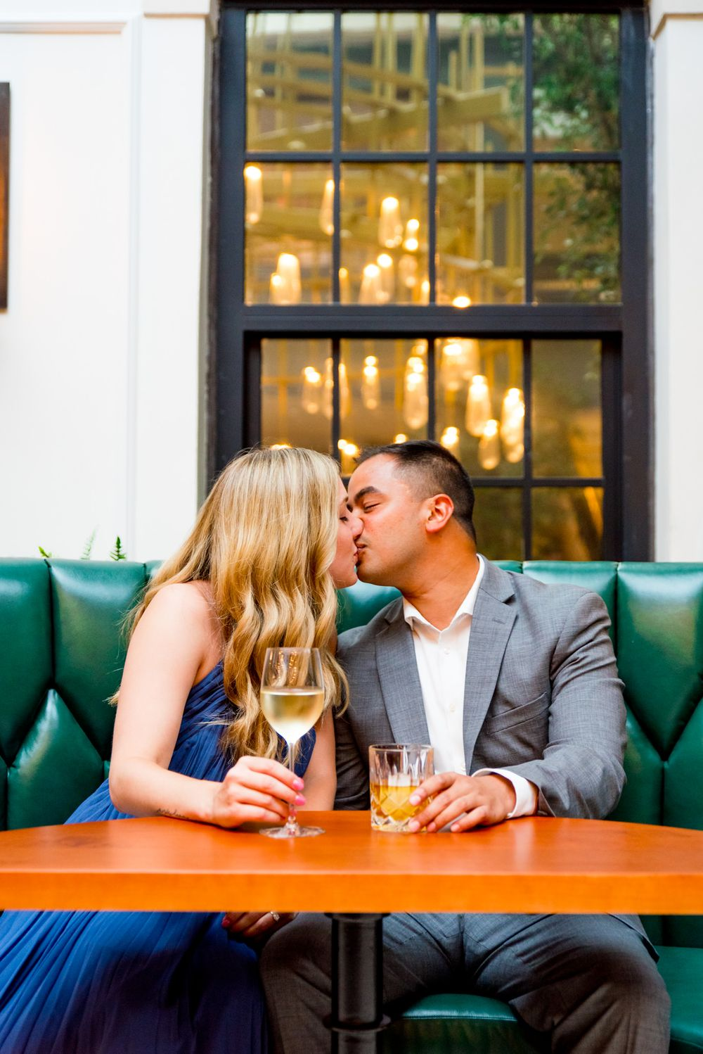 Asian man and blonde woman kiss in green booth at Lytle Park Hotel engagement session