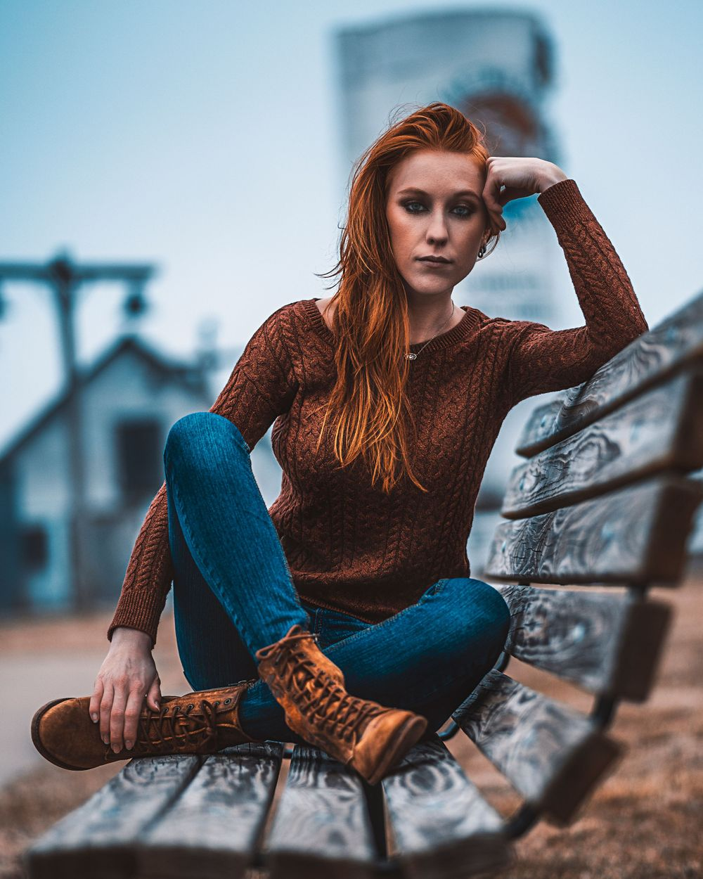 Fashion Portrait of girl in sweater jeans and boots sitting on bench for model portfolio