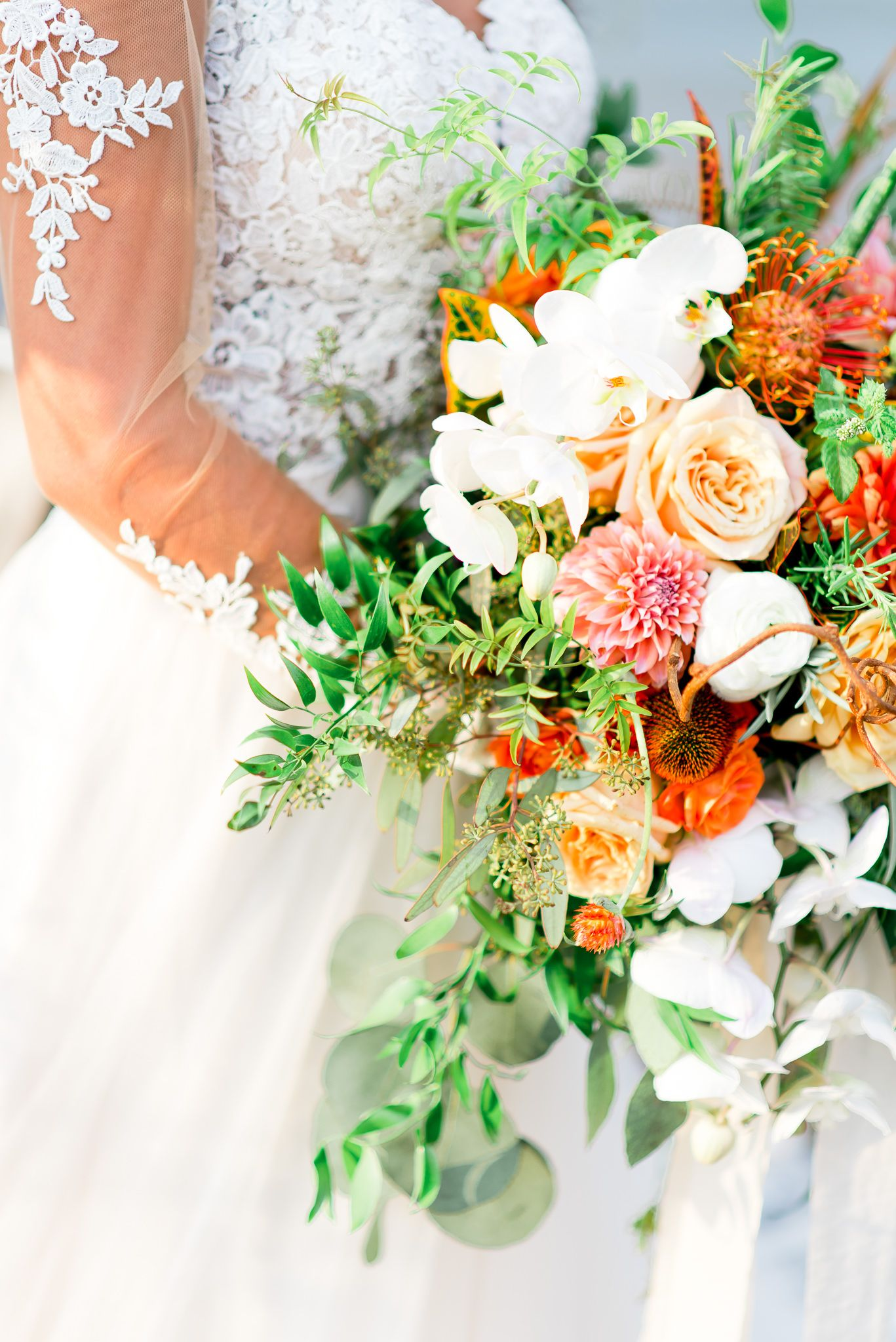 bride in lace sleeves holds an orange wedding bouquet with roses and dahlias