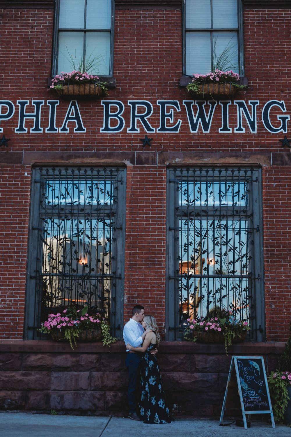 A couple in an engagement shoot in Philadelphia by a brewing company