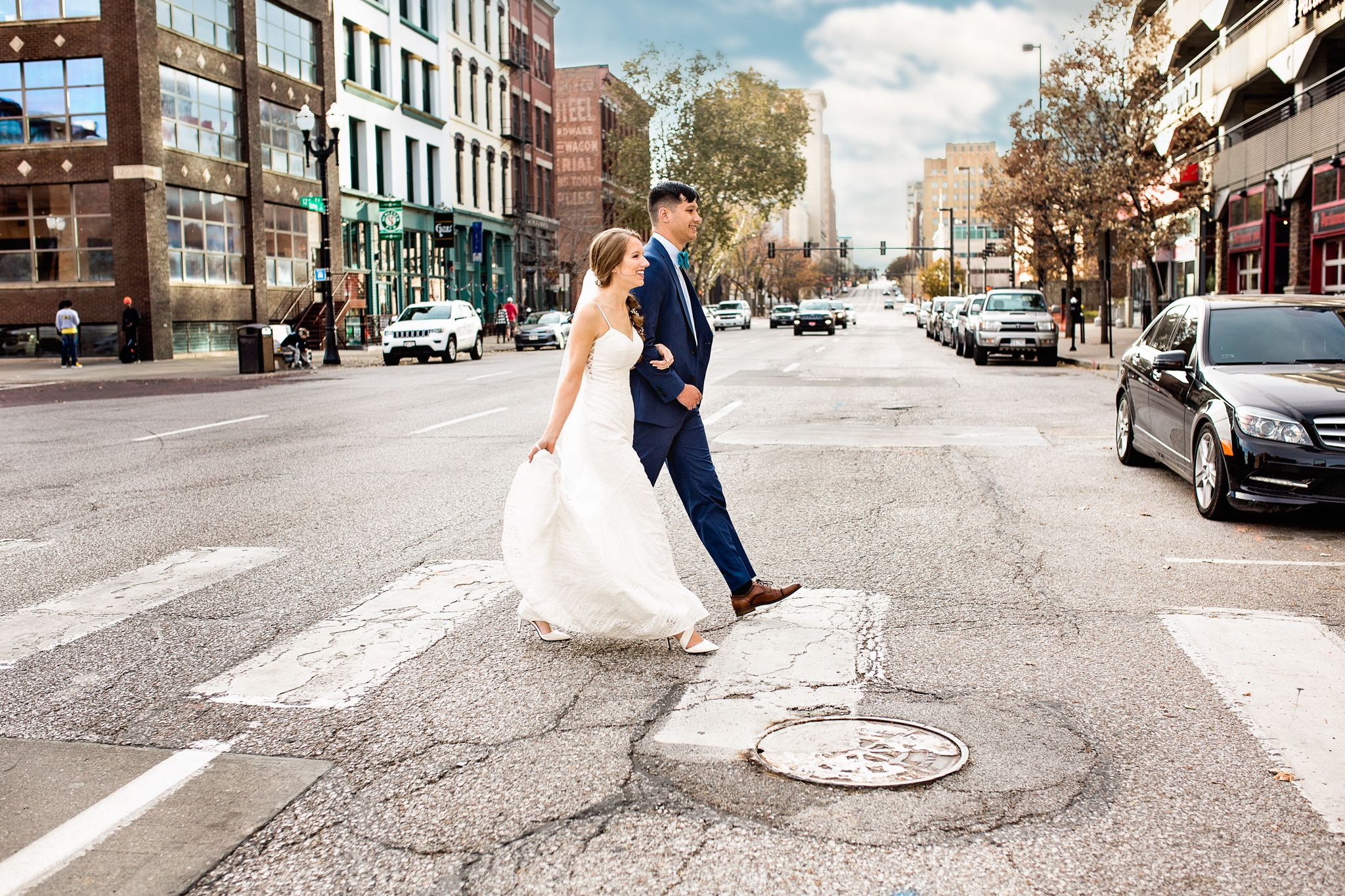 A bride and groom walk on crosswalk in downtown Omaha