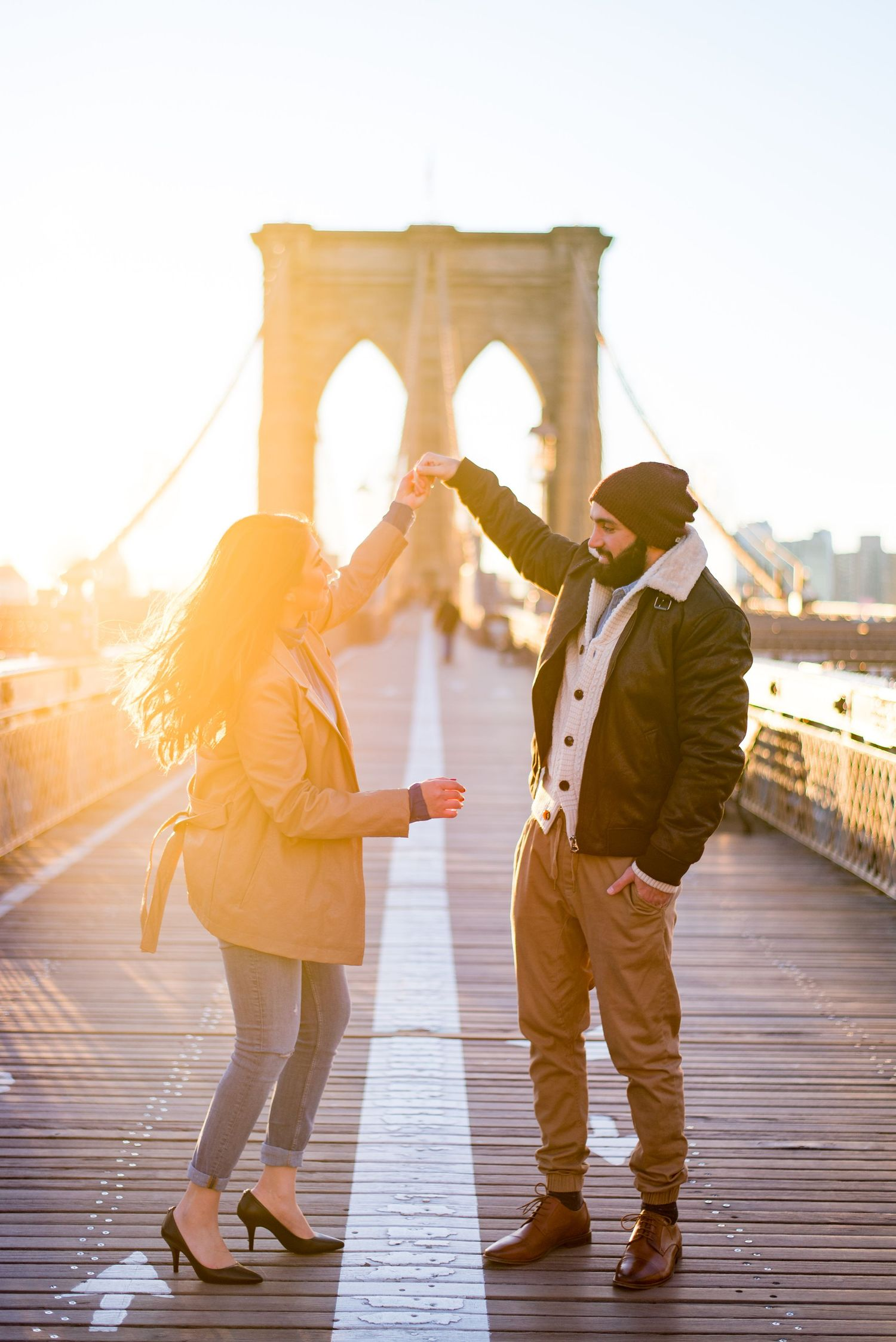 engaged man and woman twirling around in the middle of the Brooklyn Bridge in the morning at sunrise