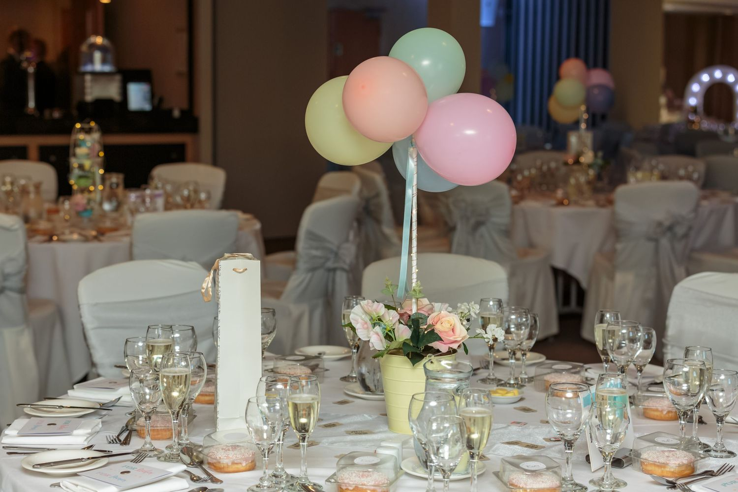 fairground theme continues inside for the wedding reception balloons and fairy cake Ferris wheels on the tables