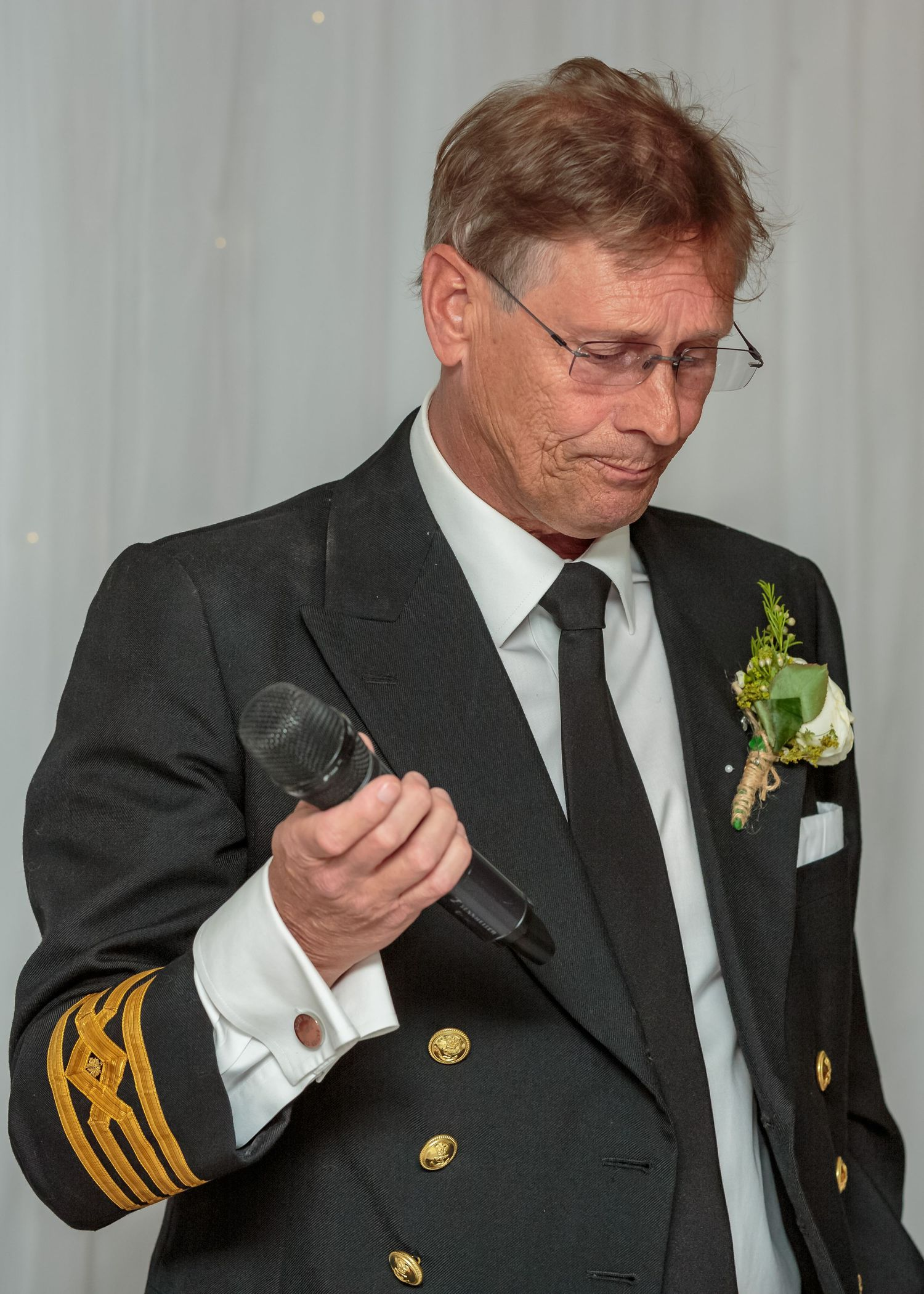 father of the bride wearing his pilot outfit holds the microphone looking upset during his speech